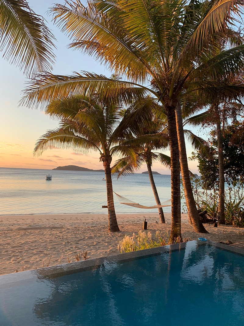 A view of the sun setting over the island from a private pool on the beach