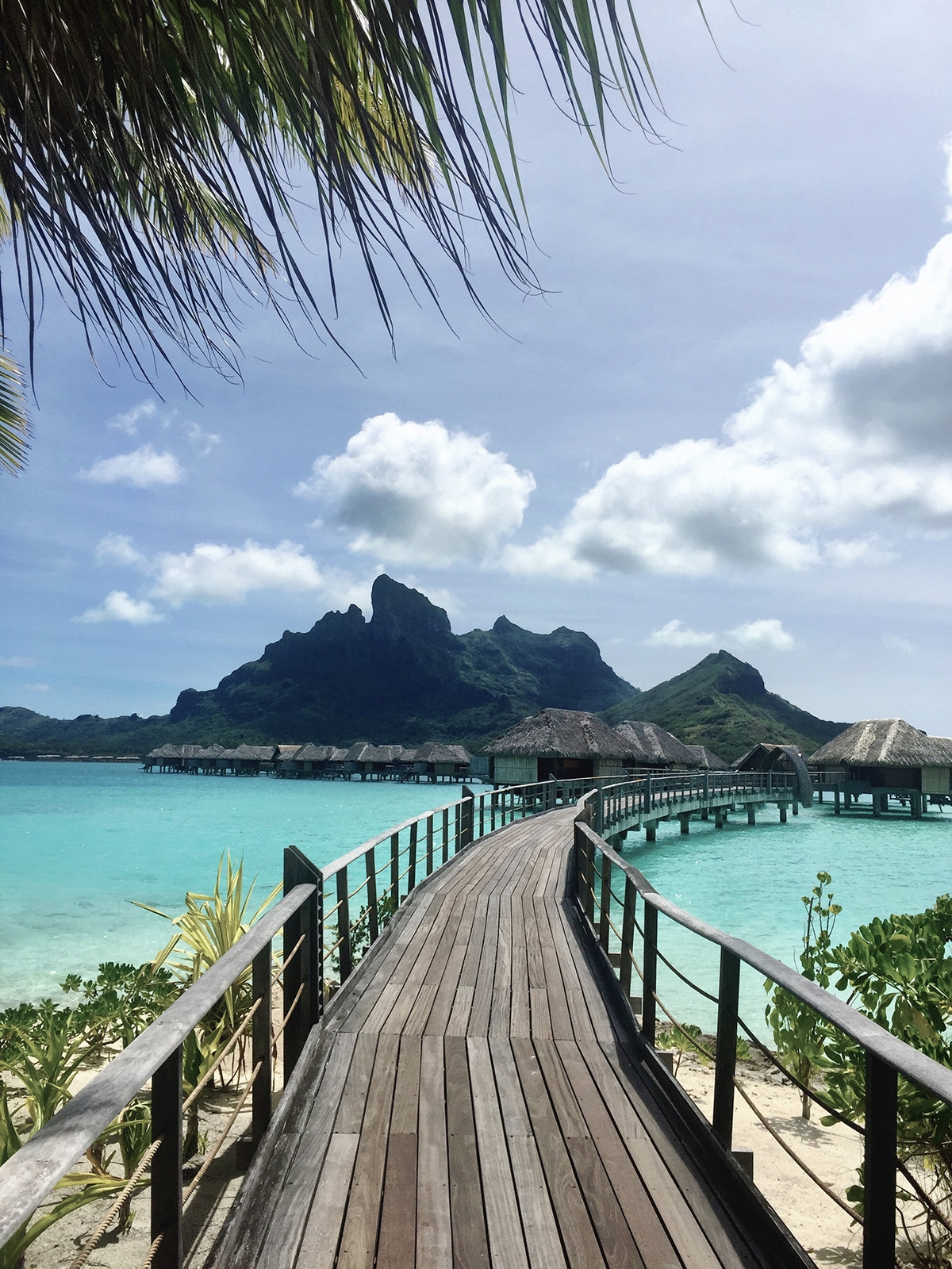 A wooden boardwalk leads to floating ocean villas with Mount Otemanu set in the background