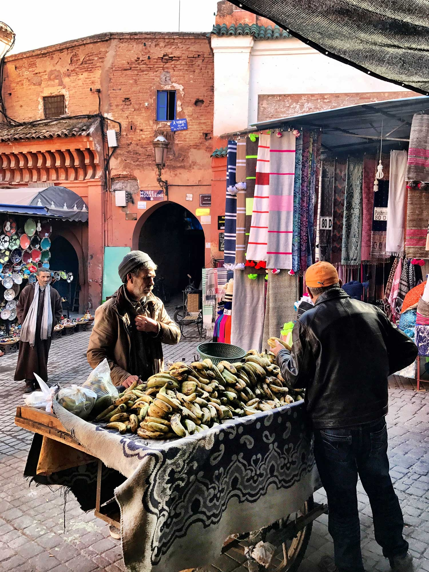 A man sells bananas on a large table in the laneways of the souks