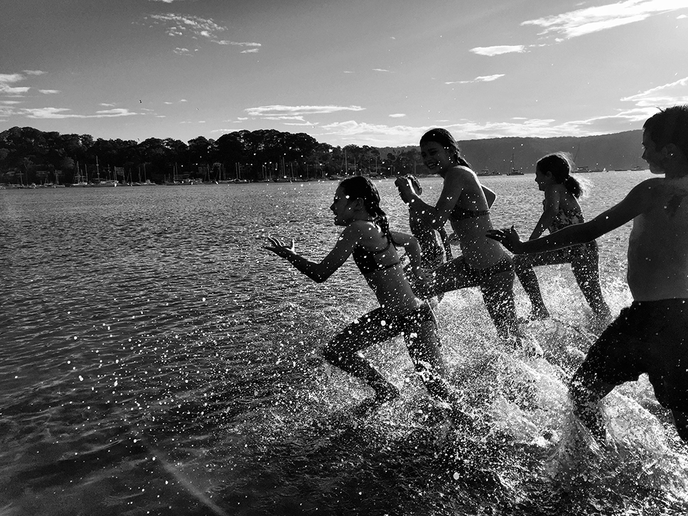 A black and white image of kids running through the seawater along the beach