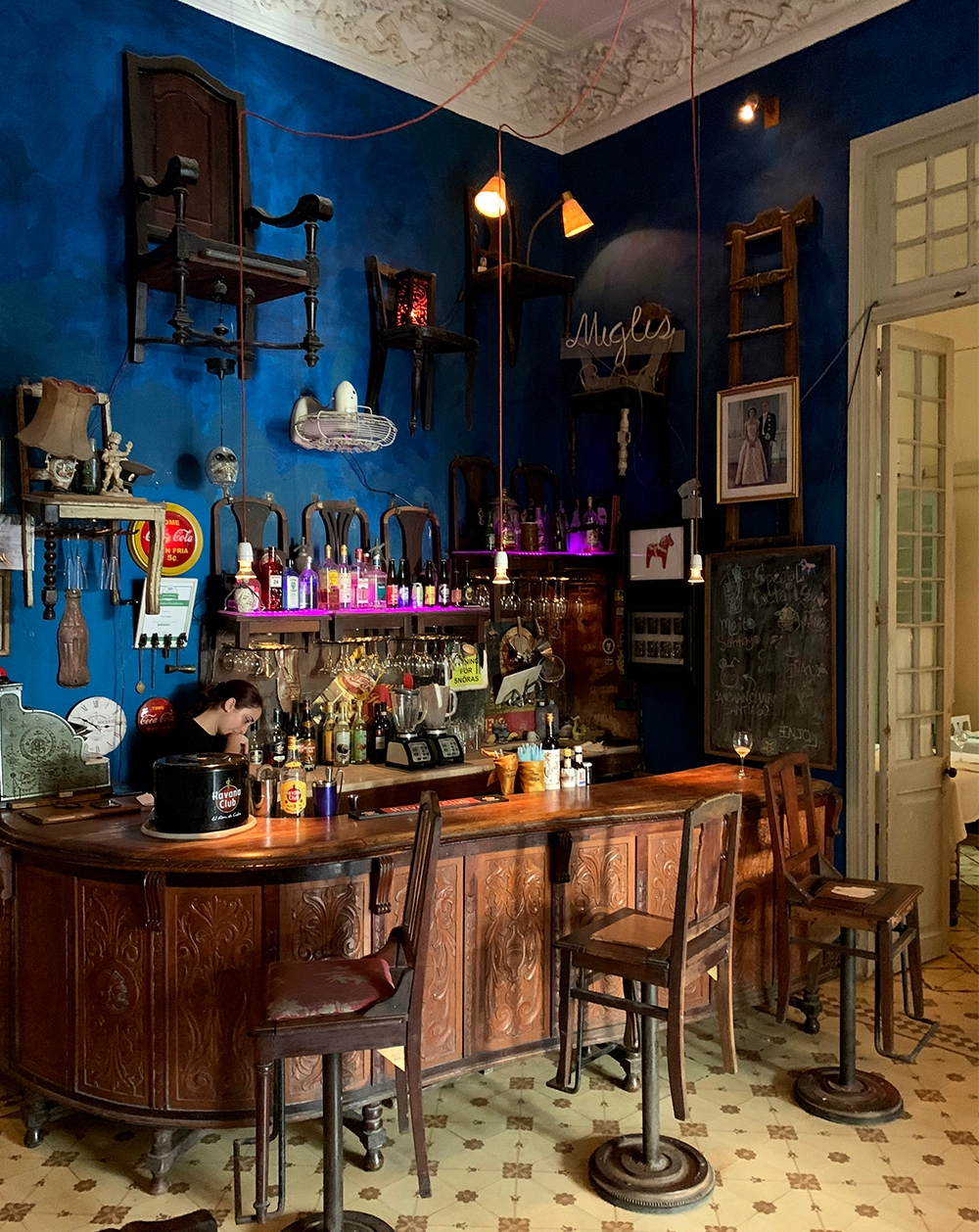 The eclectic interior of restaurant, La Guarida Paladar, sees chairs suspended to royal blue walls, hanging lights and a dark wooden bar complete with alcohol and blenders