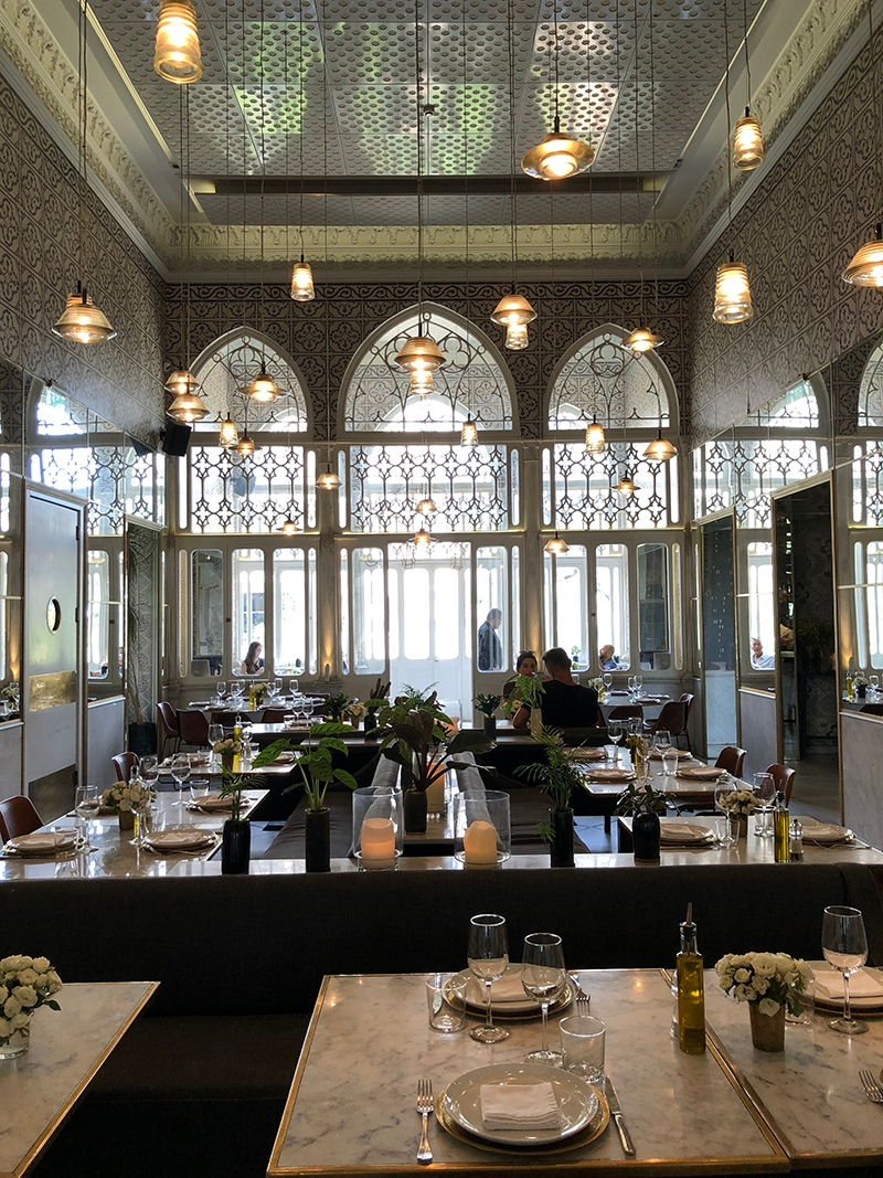 The modern interior of restaurant, Liza Beirut, features marble tables, hanging lights and a tiled ceiling
