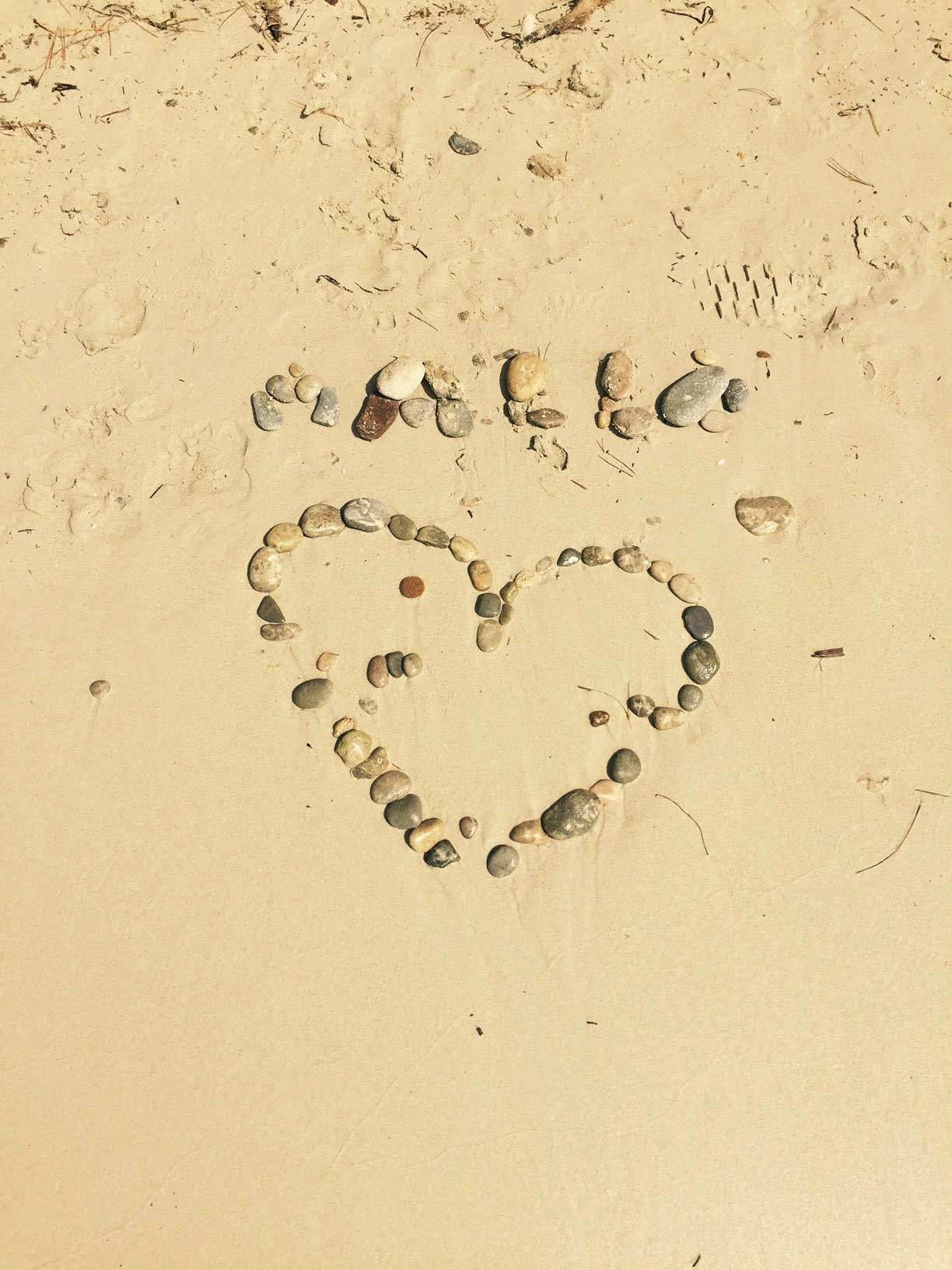 """Malla"", followed by a heart, is written in rocks on the sand at a beach"