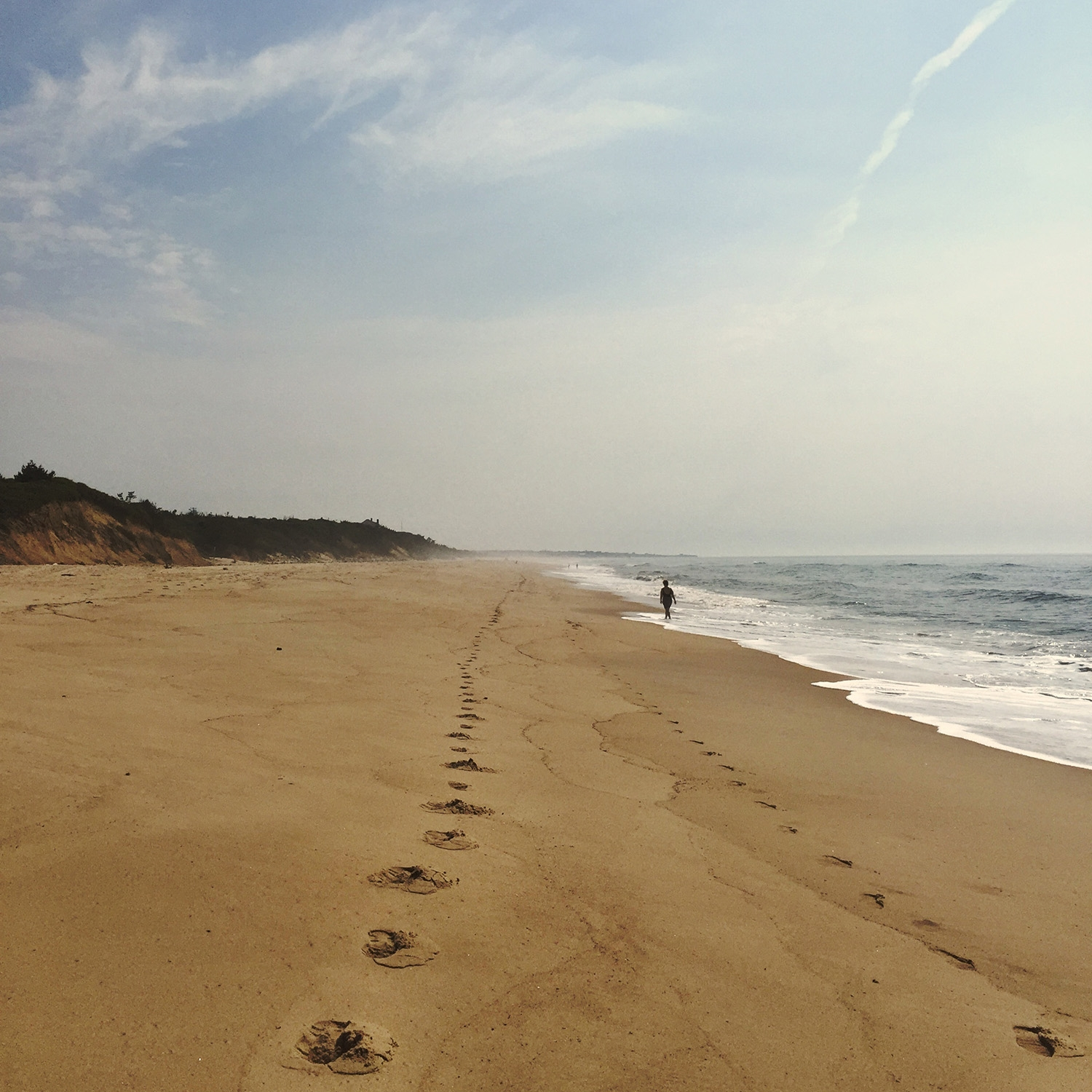 Footprints lead along the shoreline of Montauk beach and a person stands in the shallow white foam facing the horizon