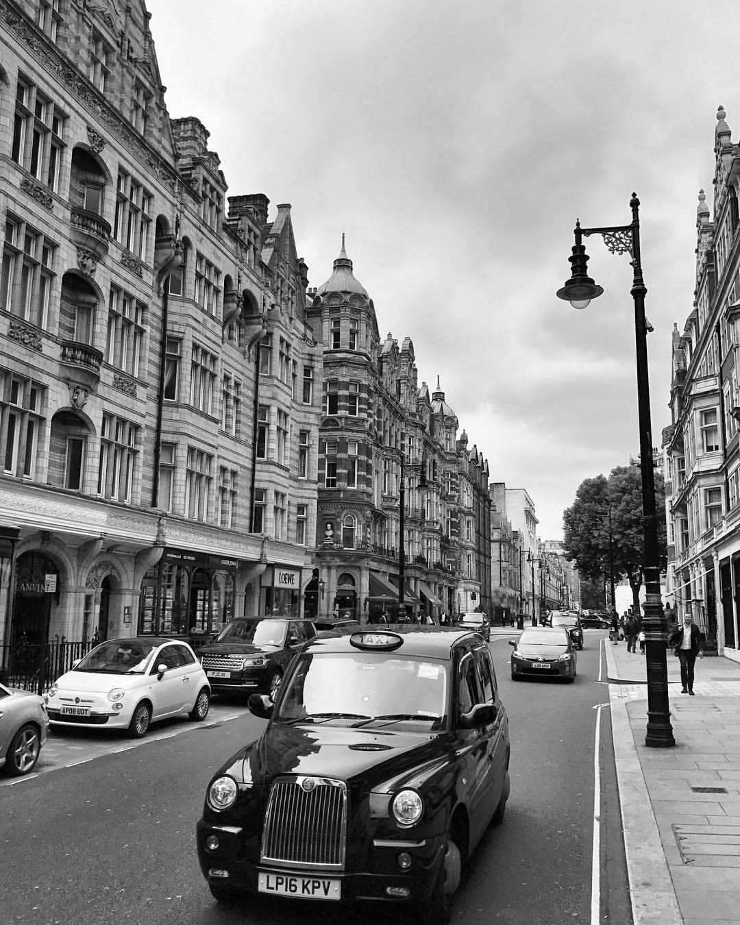 A gloomy day on Mount Street with cars passing by English baroque architectural buildings