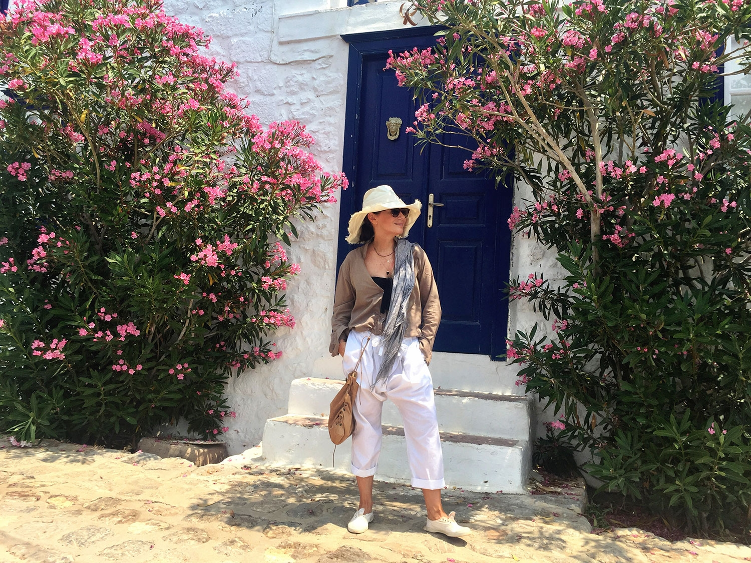 Nicky Zimmermann stands in front of a traditional white and blue Greek building, with native flowers either side of her