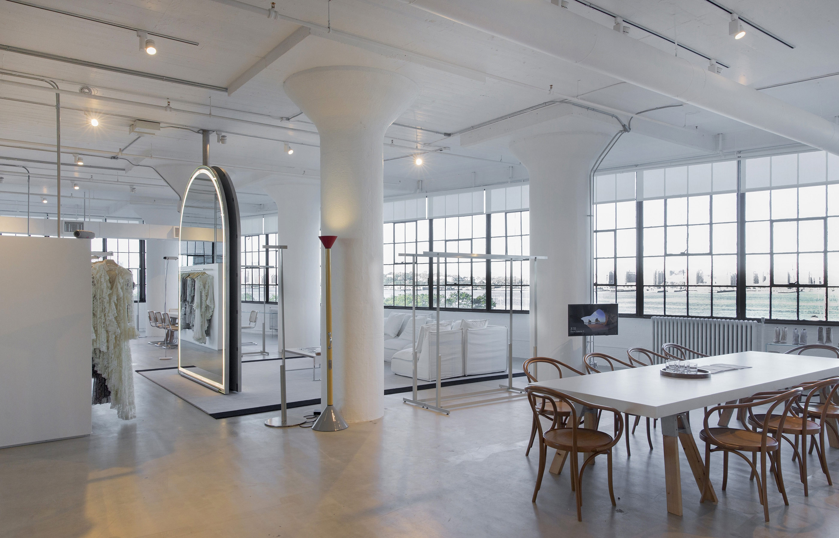 A mirror, meeting table, couch and clothing racks in our modern New York Office