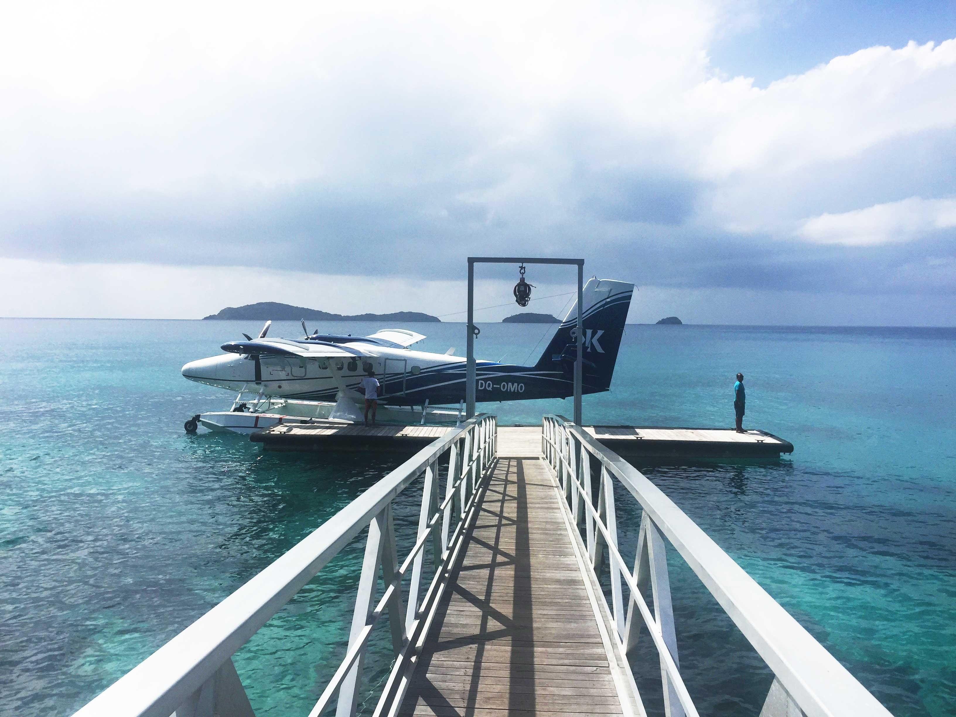 Walk to the end of the narrow pier where a seaplane waits on clear turquoise waters