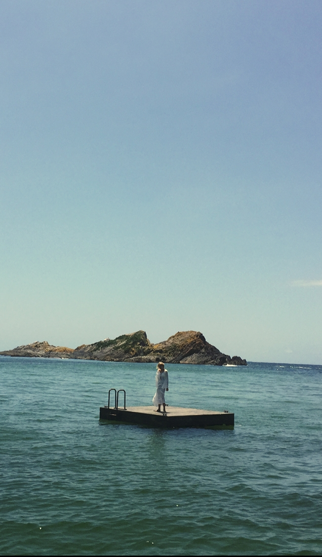 Lily Donaldson standing on a jetty in the ocean with large rock formations in the background