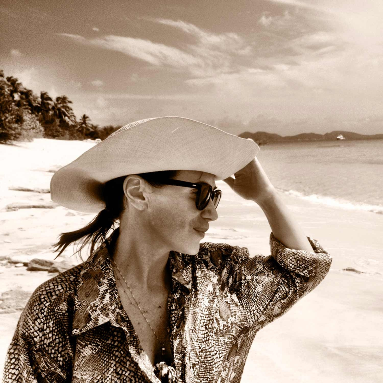 Nicky Zimmermann holding her hat on the coastline