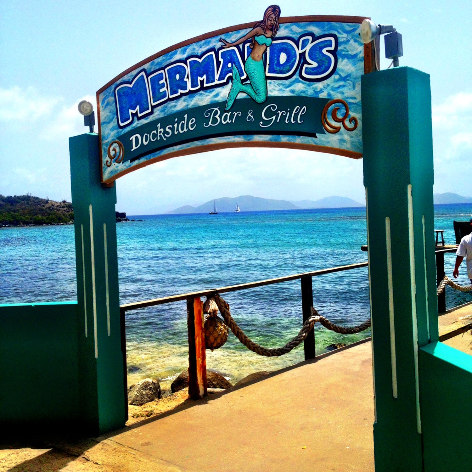 An archway advertising 'Mermaid's Dockside Bar and Grill' with a walkway above the ocean