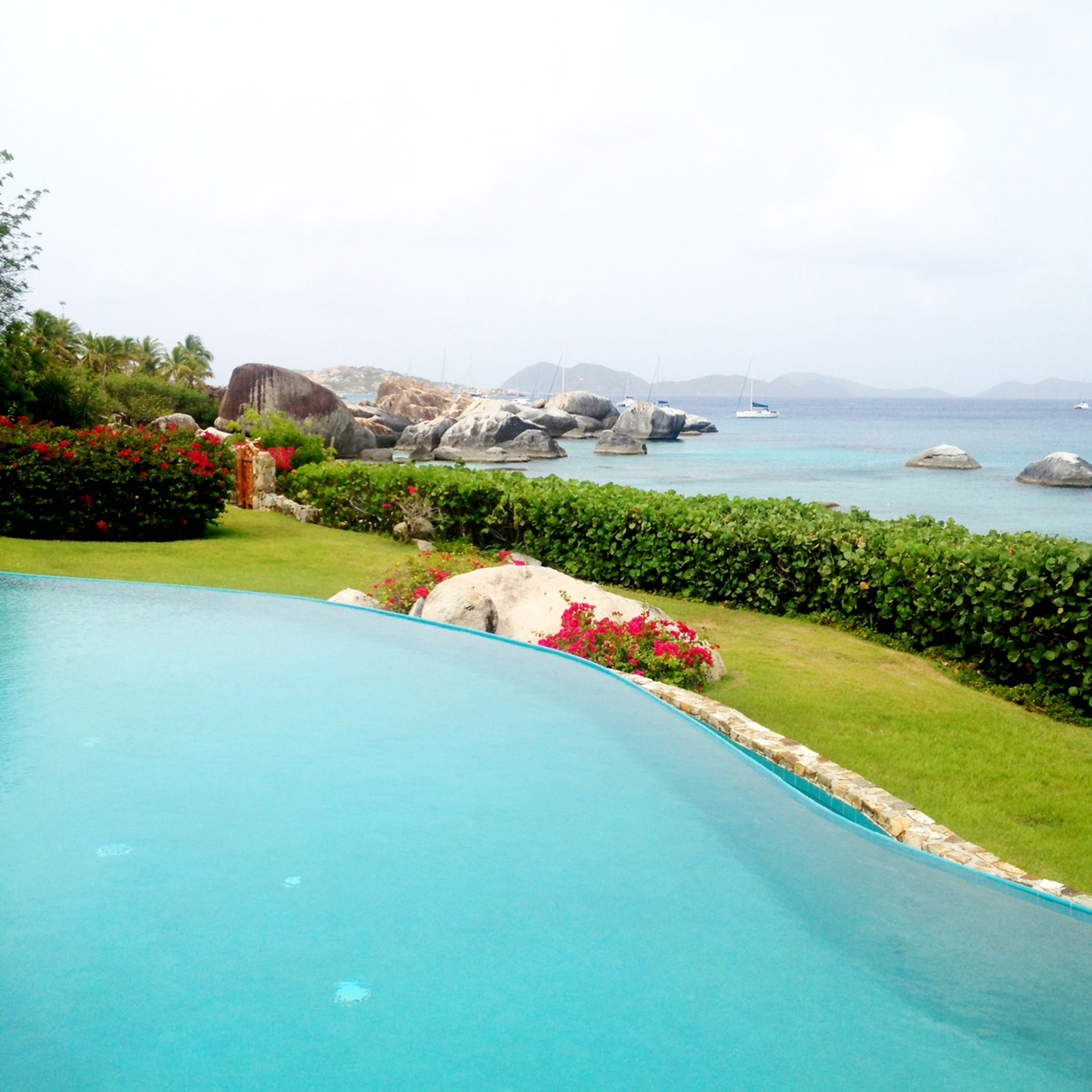 A large pool situated next to a manicured lawn and bright blue ocean