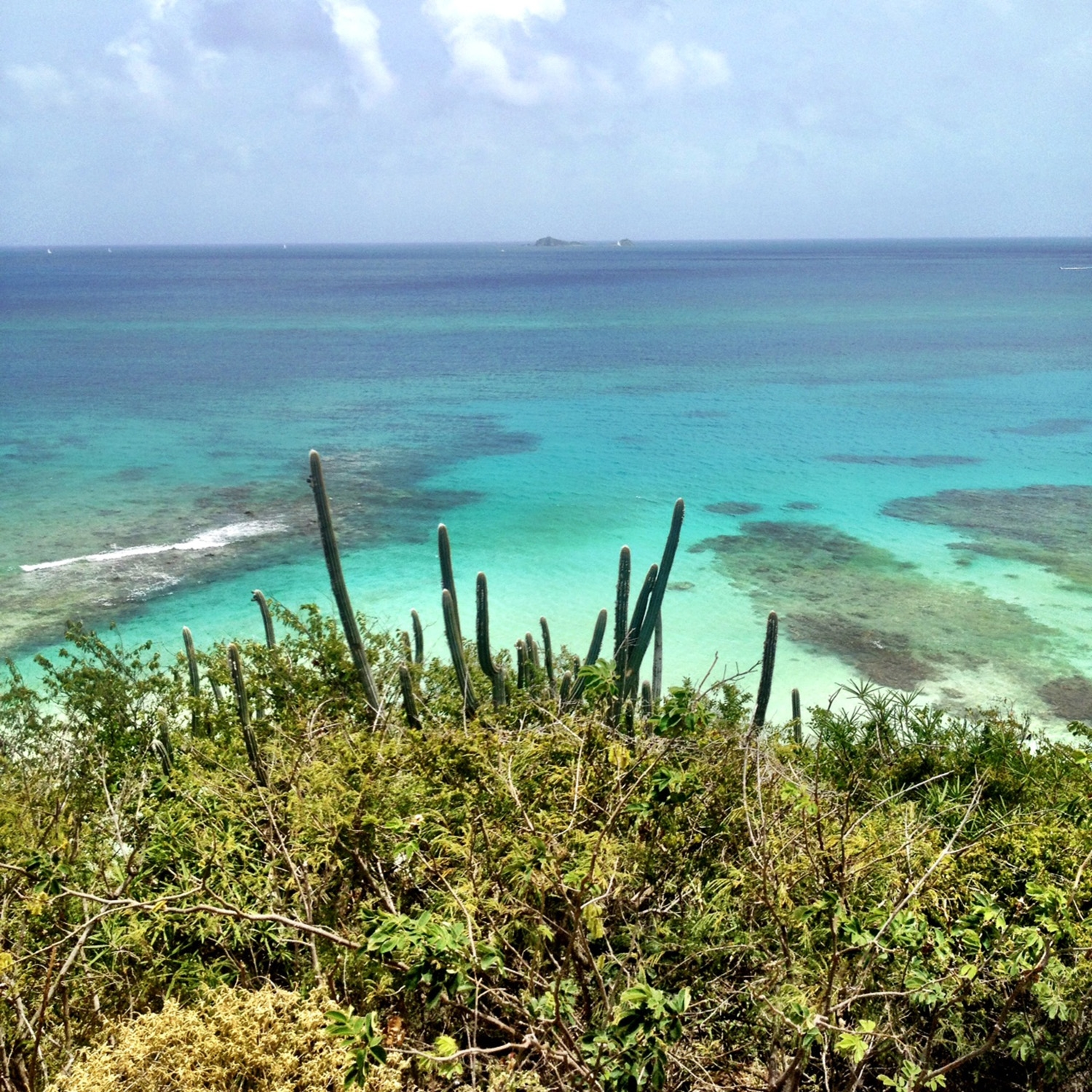 Looking down at the turquoise reefs and clear ocean water from a small hill