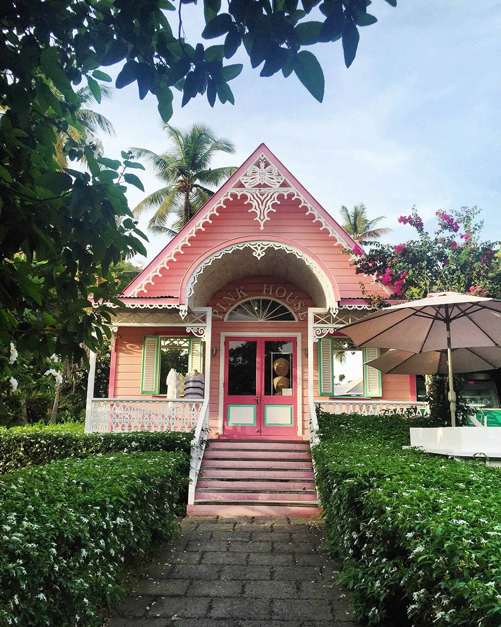 Pink House Boutique surrounded by hedges and dense gardens