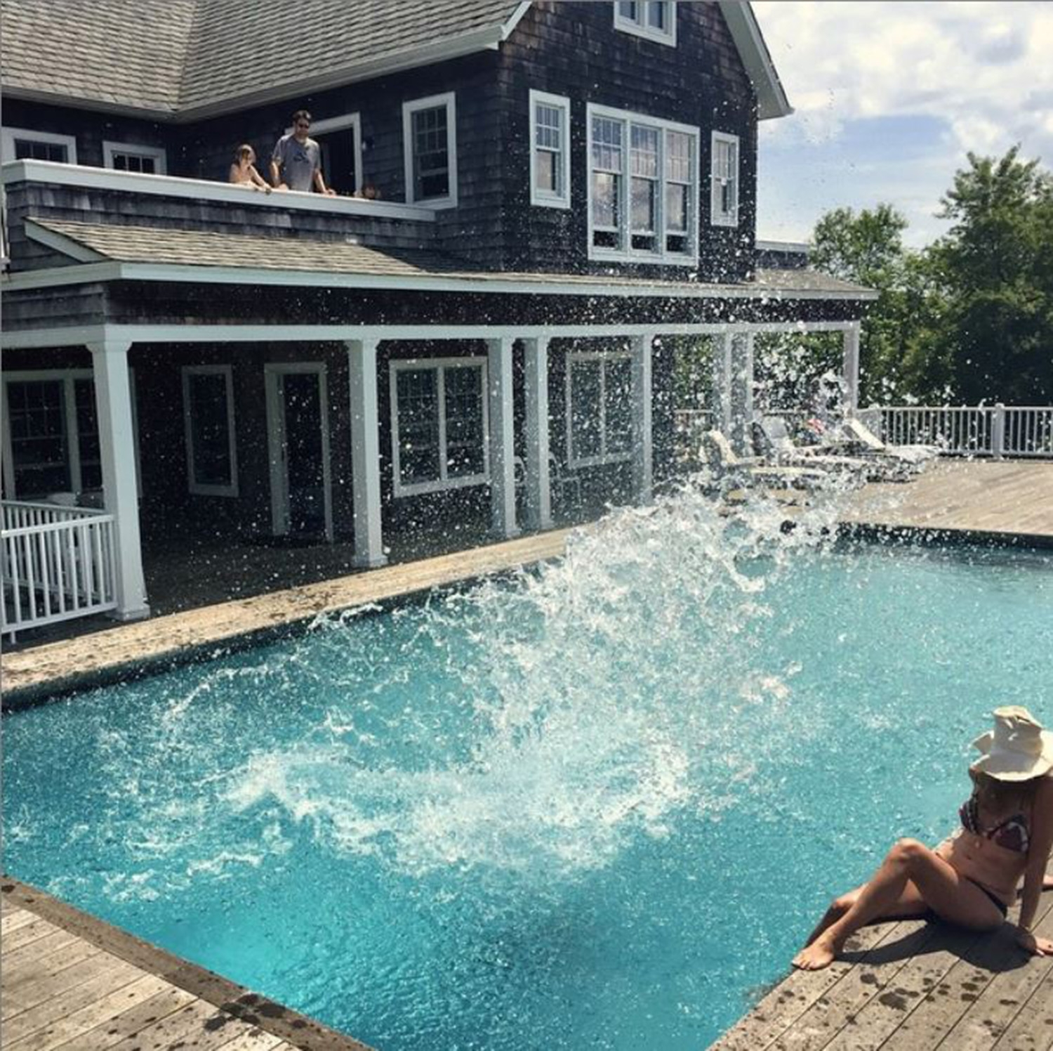 The splash of someone jumping into the pool next to a large shingle house