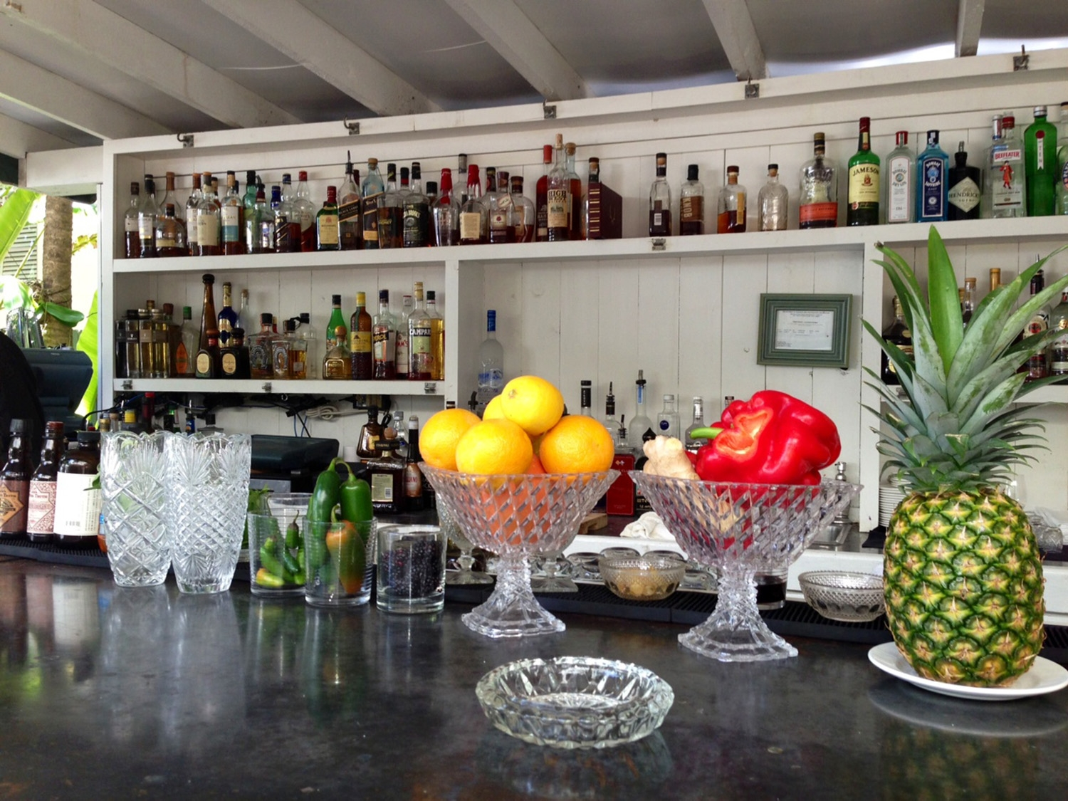 A white, wooden poolside bar has bottles of alcohol lined across the shelves on the back wall, and bowls of fruit on the bar