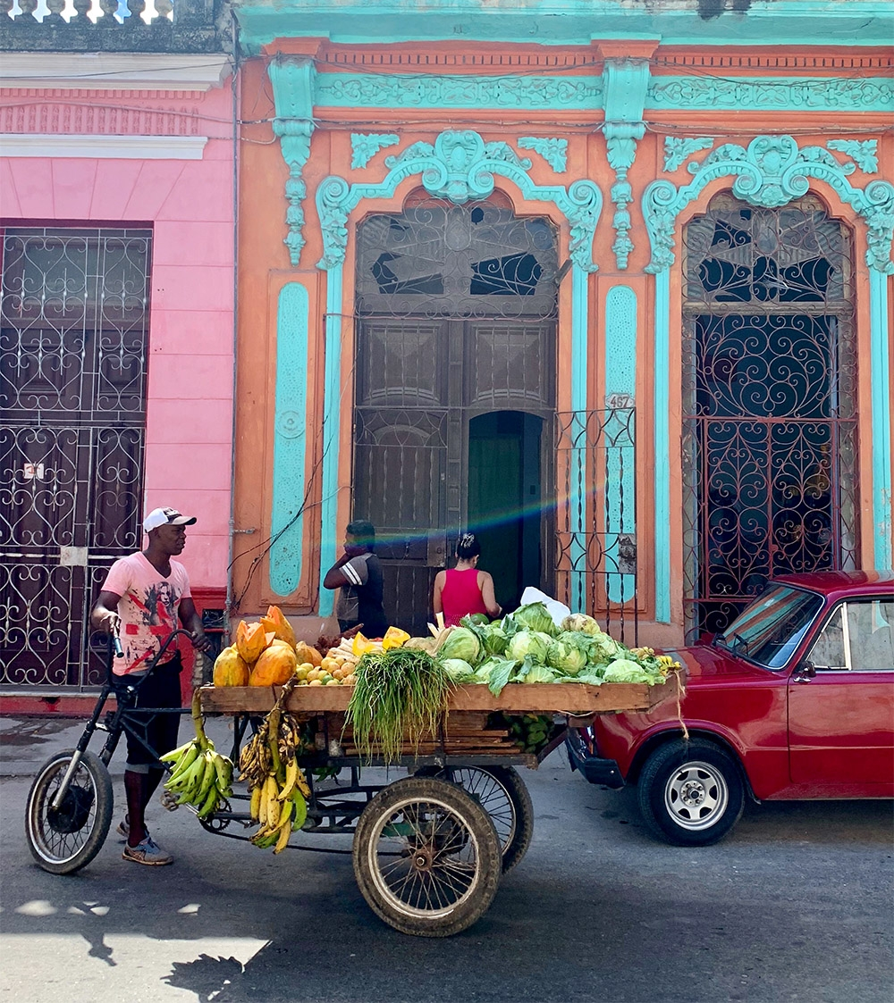 Brightly coloured buildings are on every corner, and a man sells fruit from a bike and cart