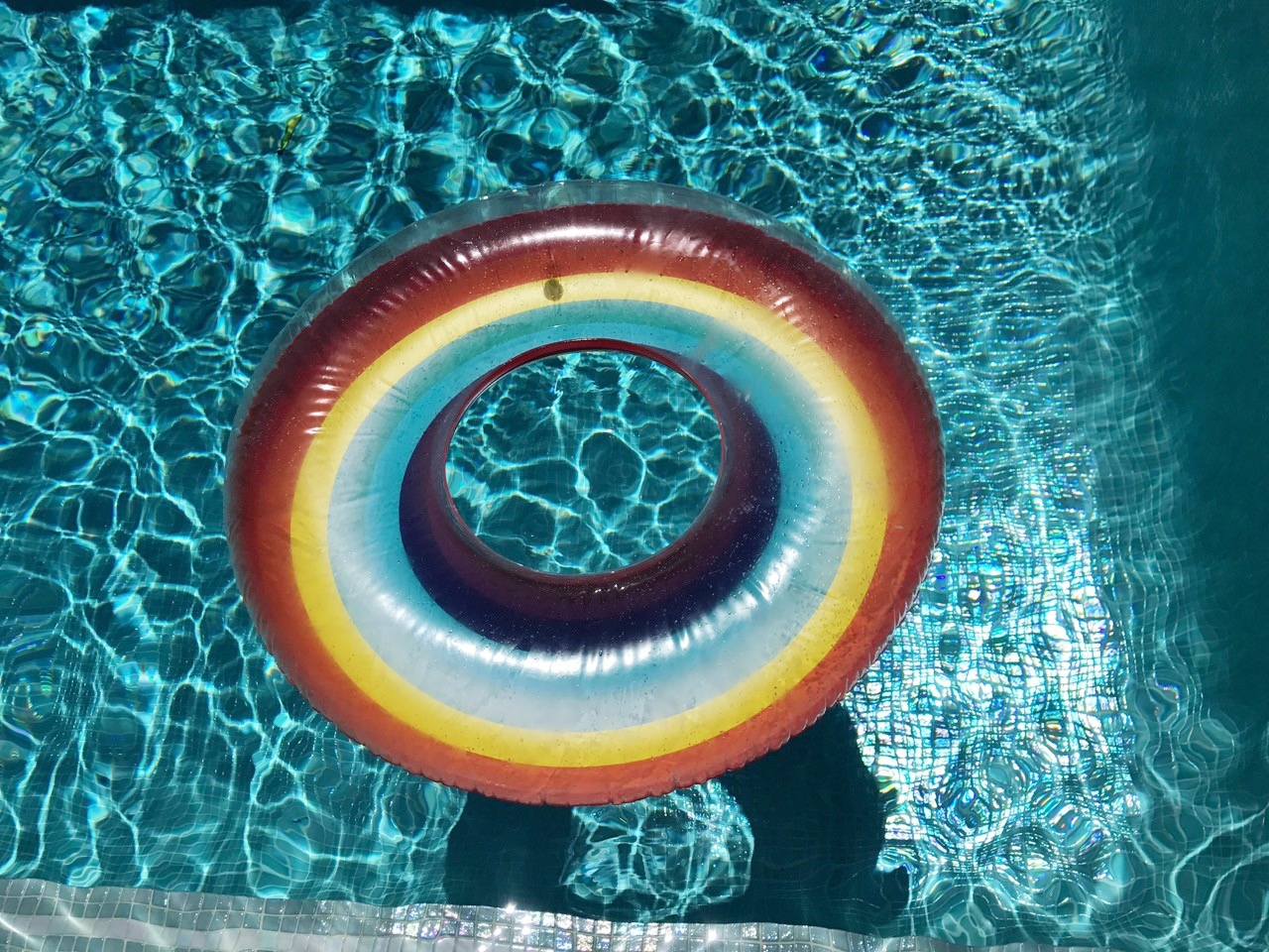A post-lunch swim with inflatable rainbow pool toys