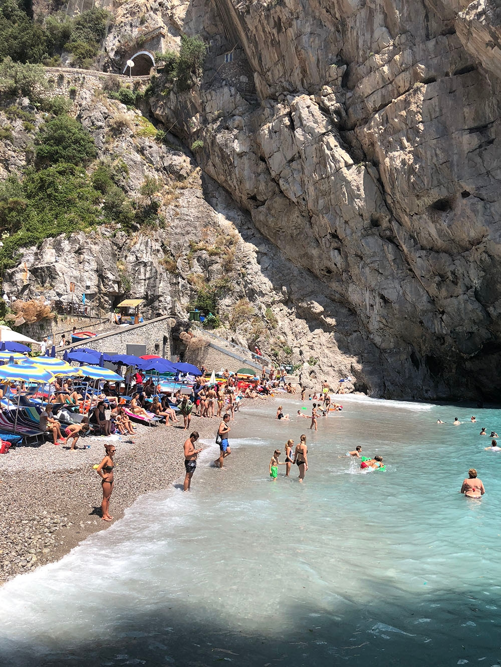 Praiano Beach is full of people, umbrellas, sun loungers and turquoise water
