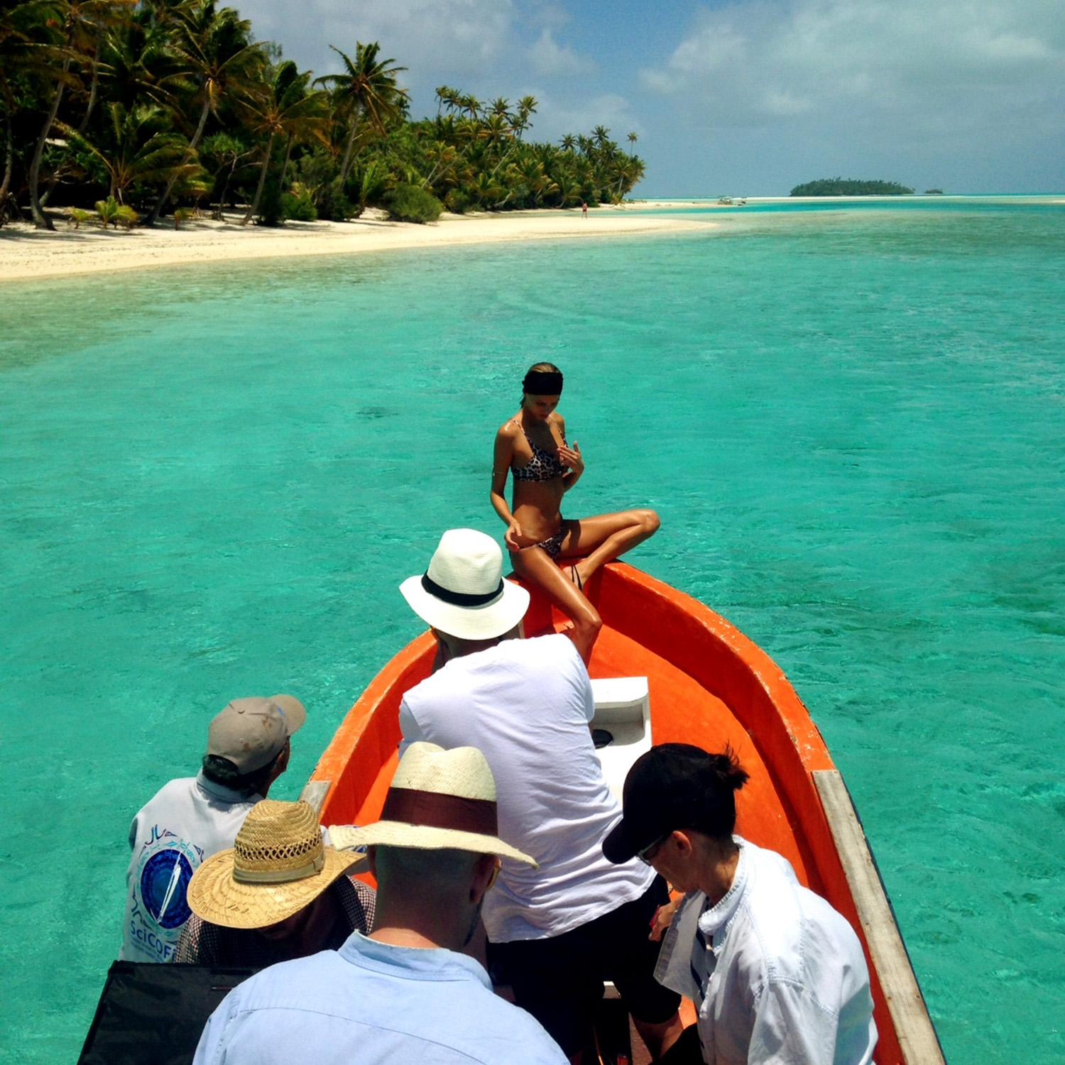 A model perched at the front of a bright orange boat poses for the photographer and team behind. Set within clear blue waters with lush green palm trees clustered along the expansive white sand of the island