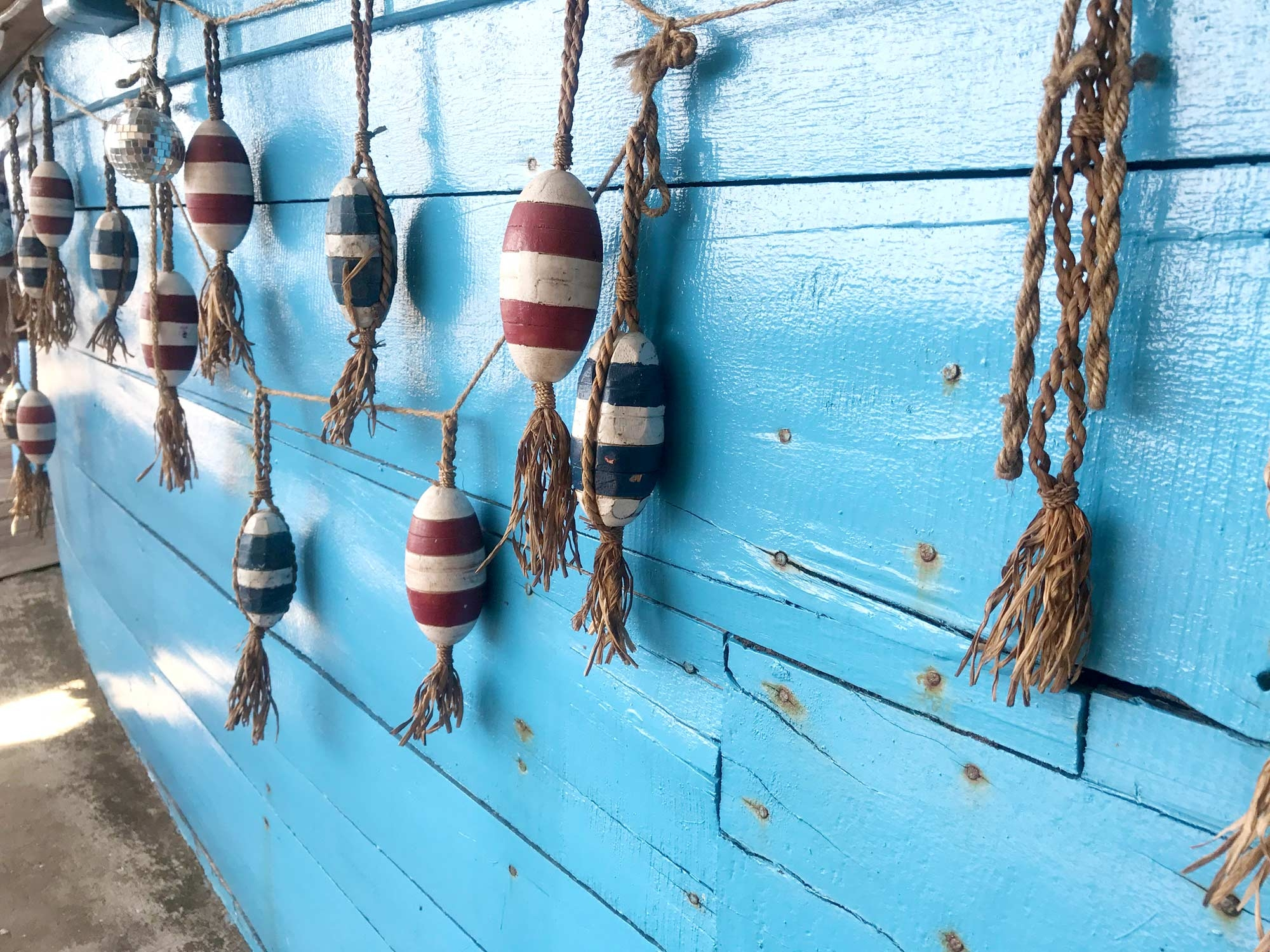 Striped buoys hung against a vibrant blue wall