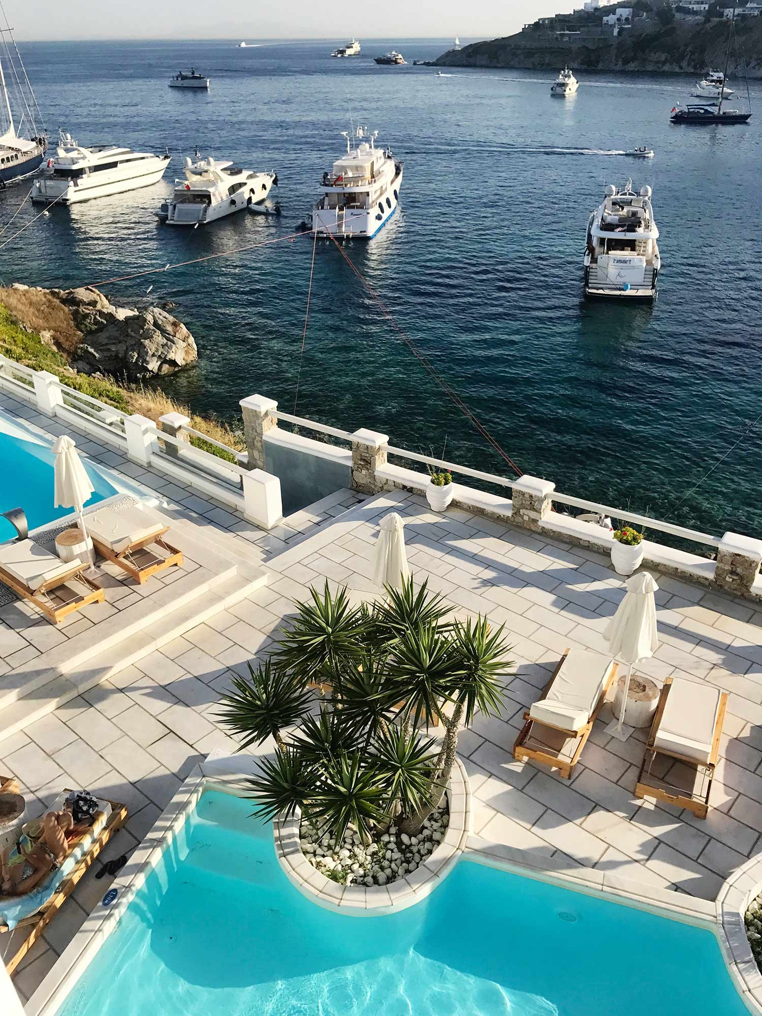 Seaside pools overlooking anchored boats and blue water. July 2017