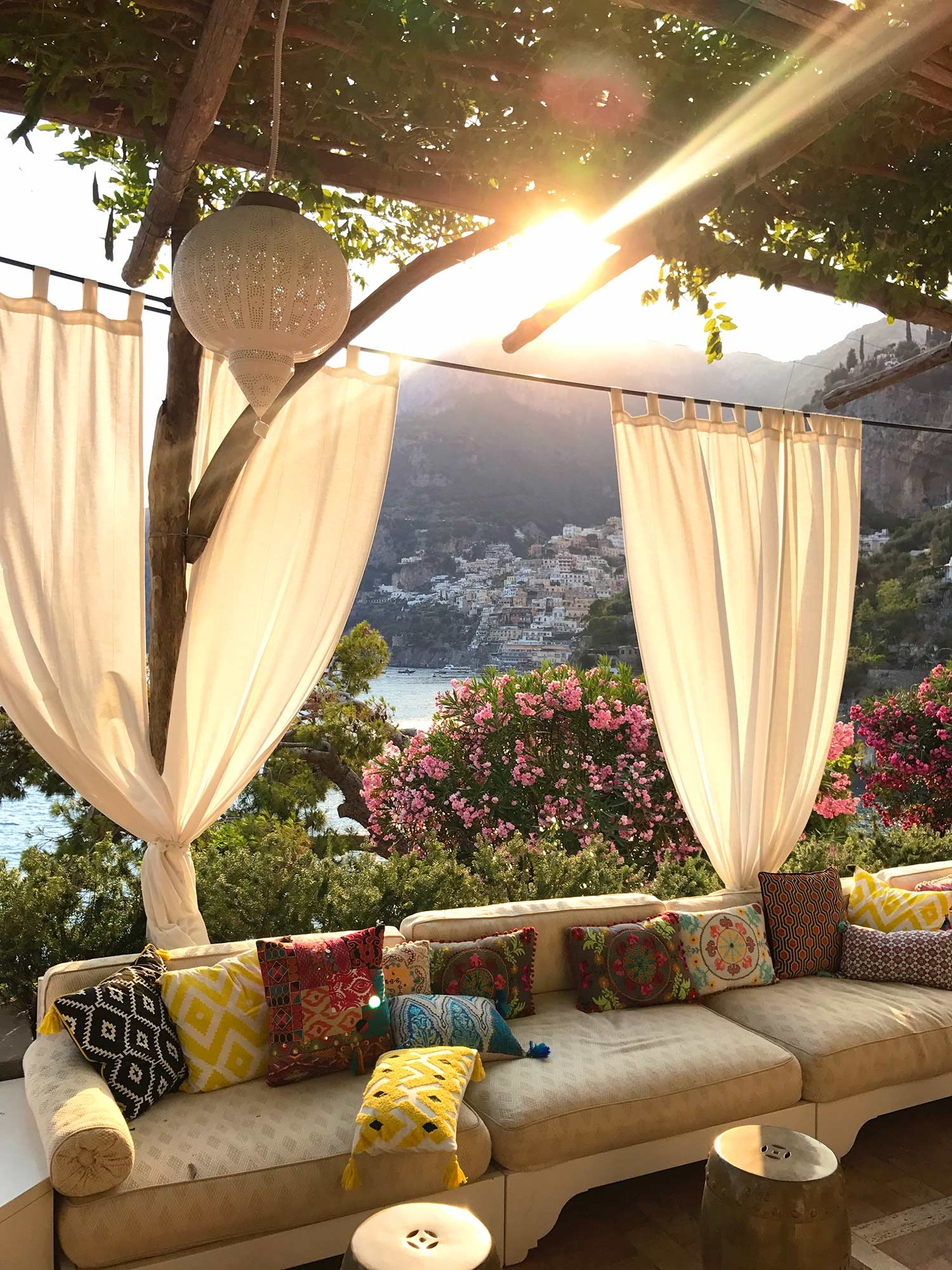 A view of the sunset over Positano from outdoor couches at Villa Tre Ville