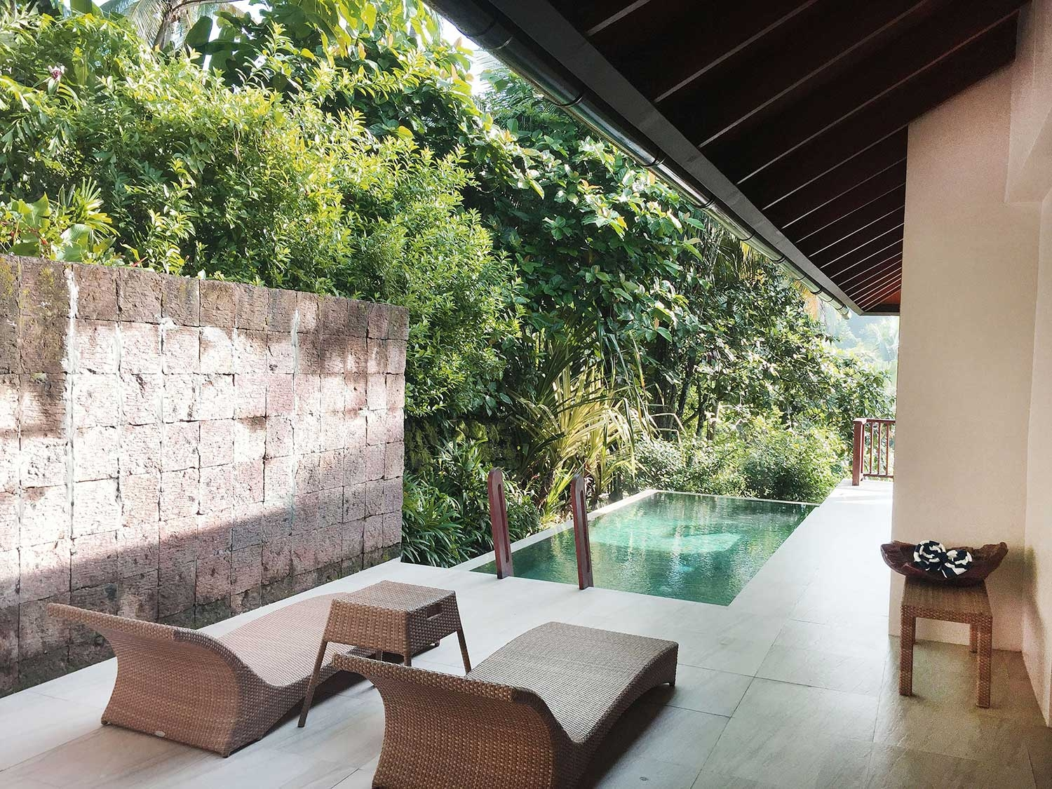 A private pool is shaded by the roof of the villa, as well as the neighbouring jungle
