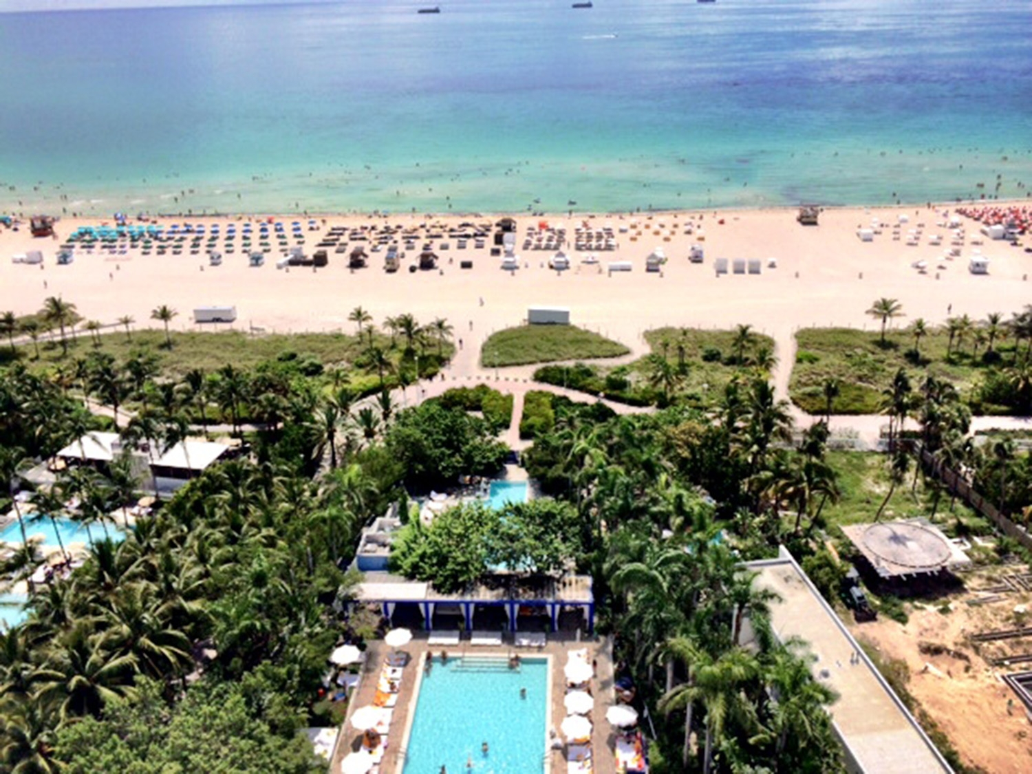The view of the hotel pool, gardens and sun loungers along the white sand of South Beach