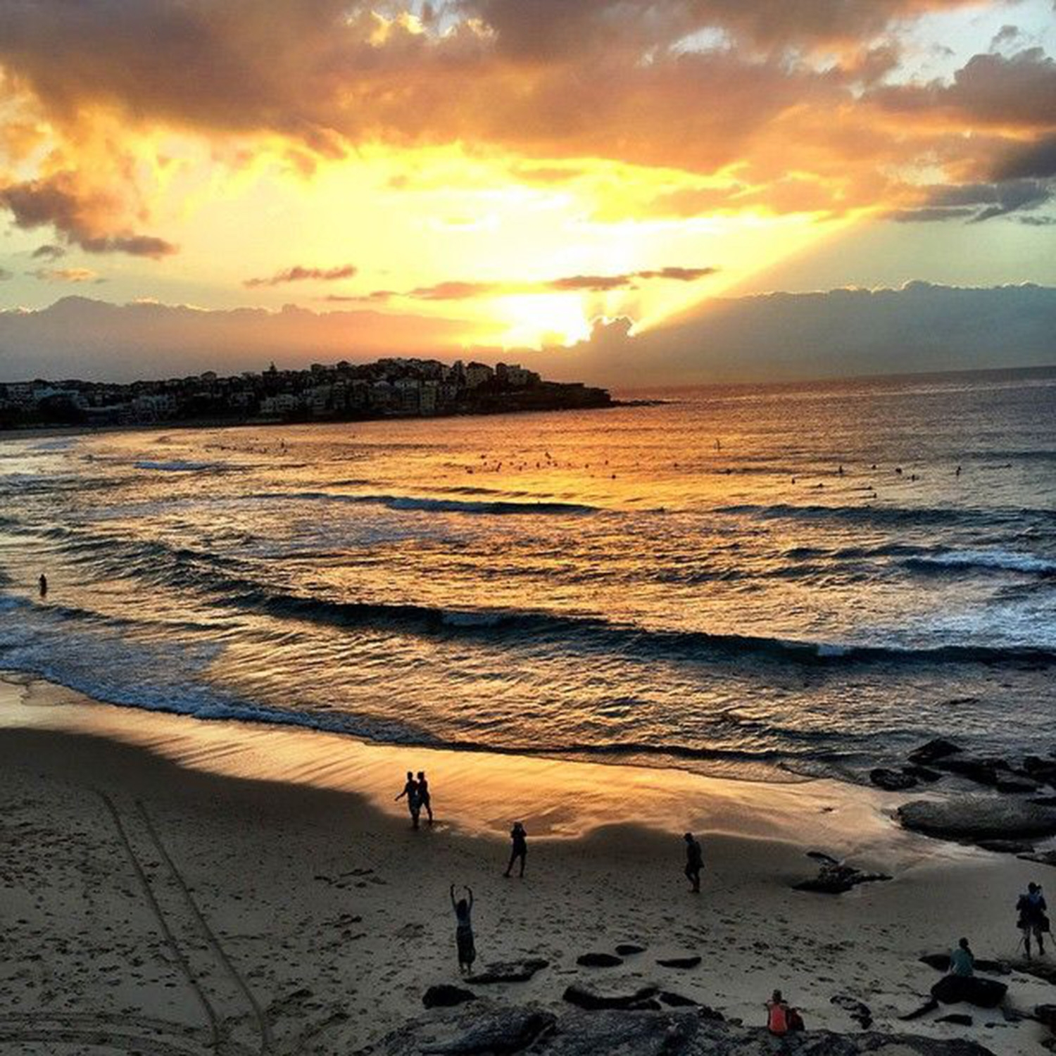 The sun setting over calm waters at South Bondi