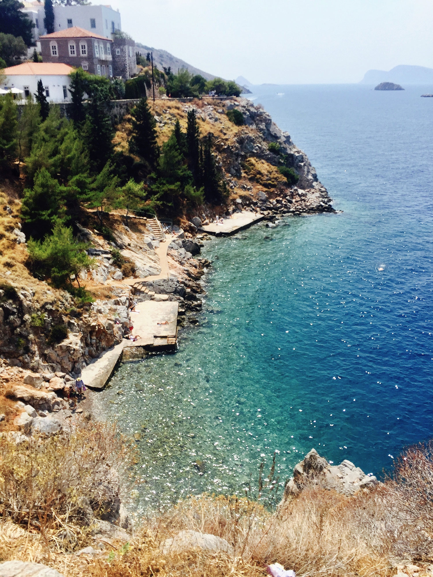 The different shades of ocean blue sparkling in a cove on the coast of Hydra