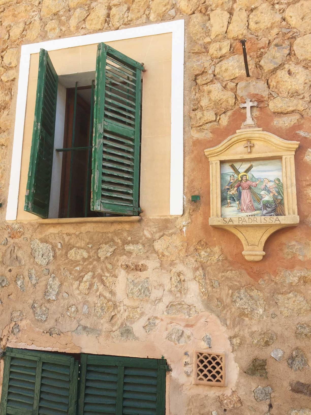 An old stone building with green shutters and religious paintings in the bohemian village of Deia
