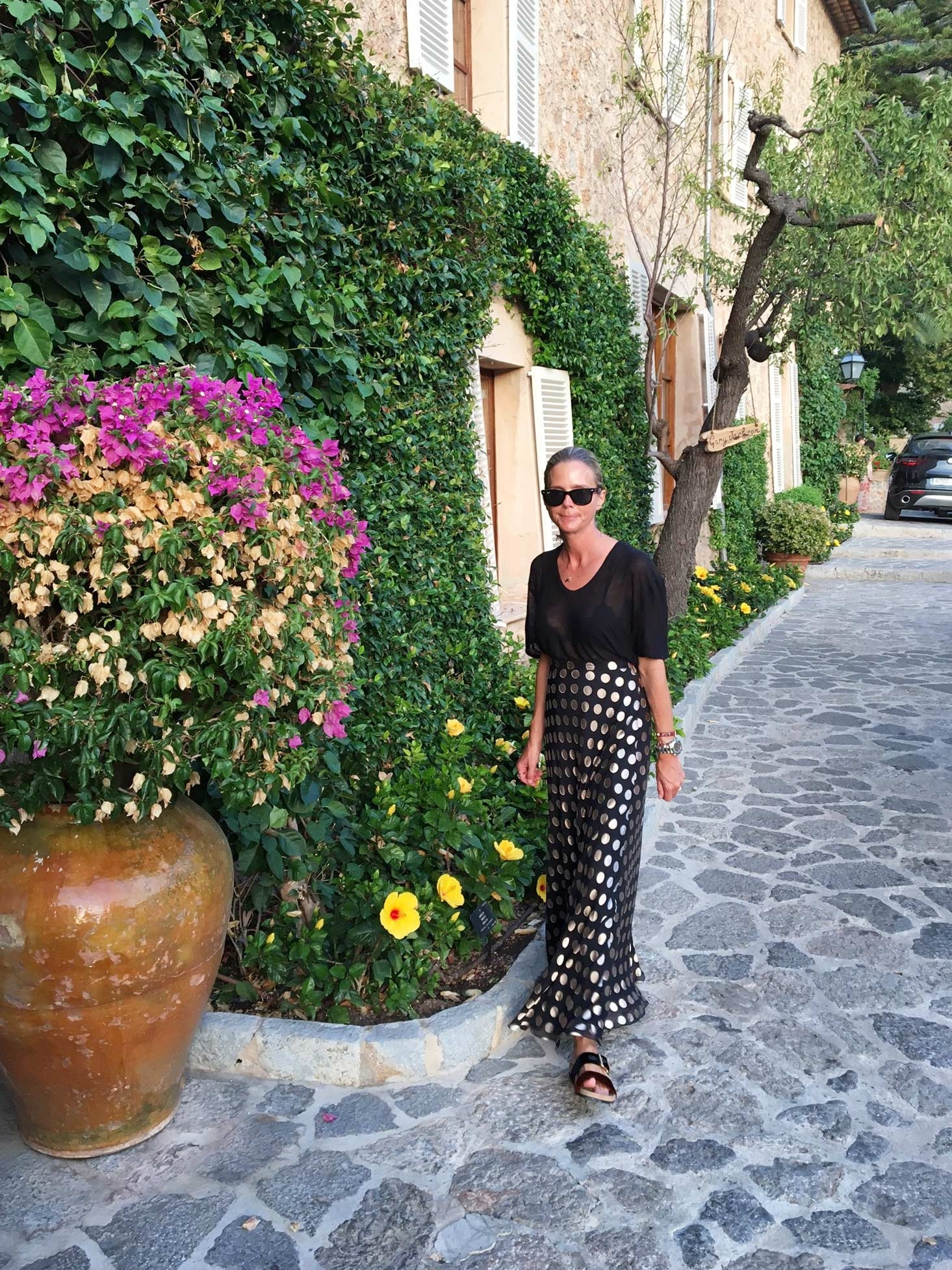 Sophie Lee strolls past lush green vines, blooming flowers and old buildings on her way to dinner