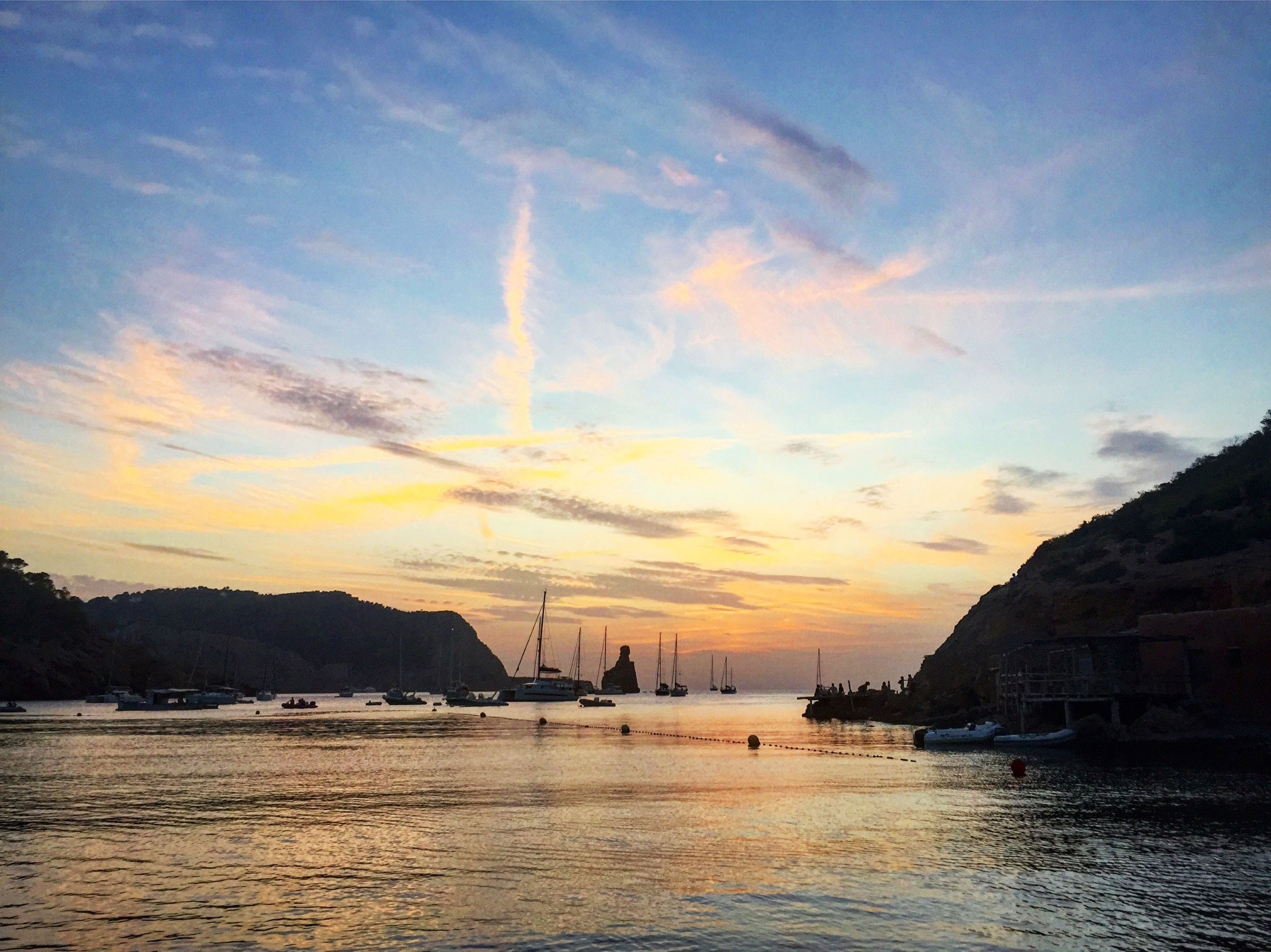 A colourful sunset over the yachts on the ocean and surrounding mountains