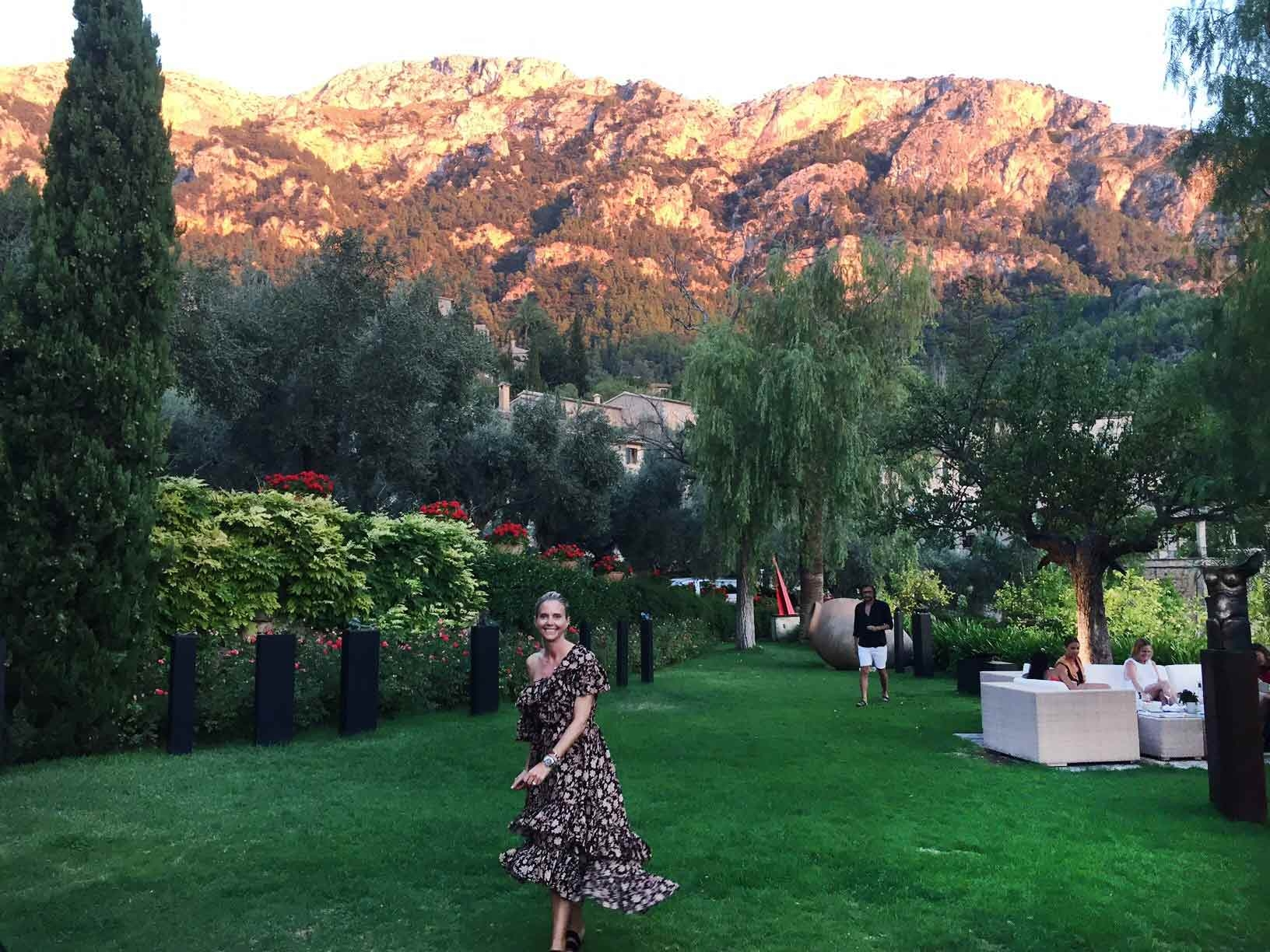 Sophie Lee stands in a garden full of lush green plants at La Residencia for sunset drinks