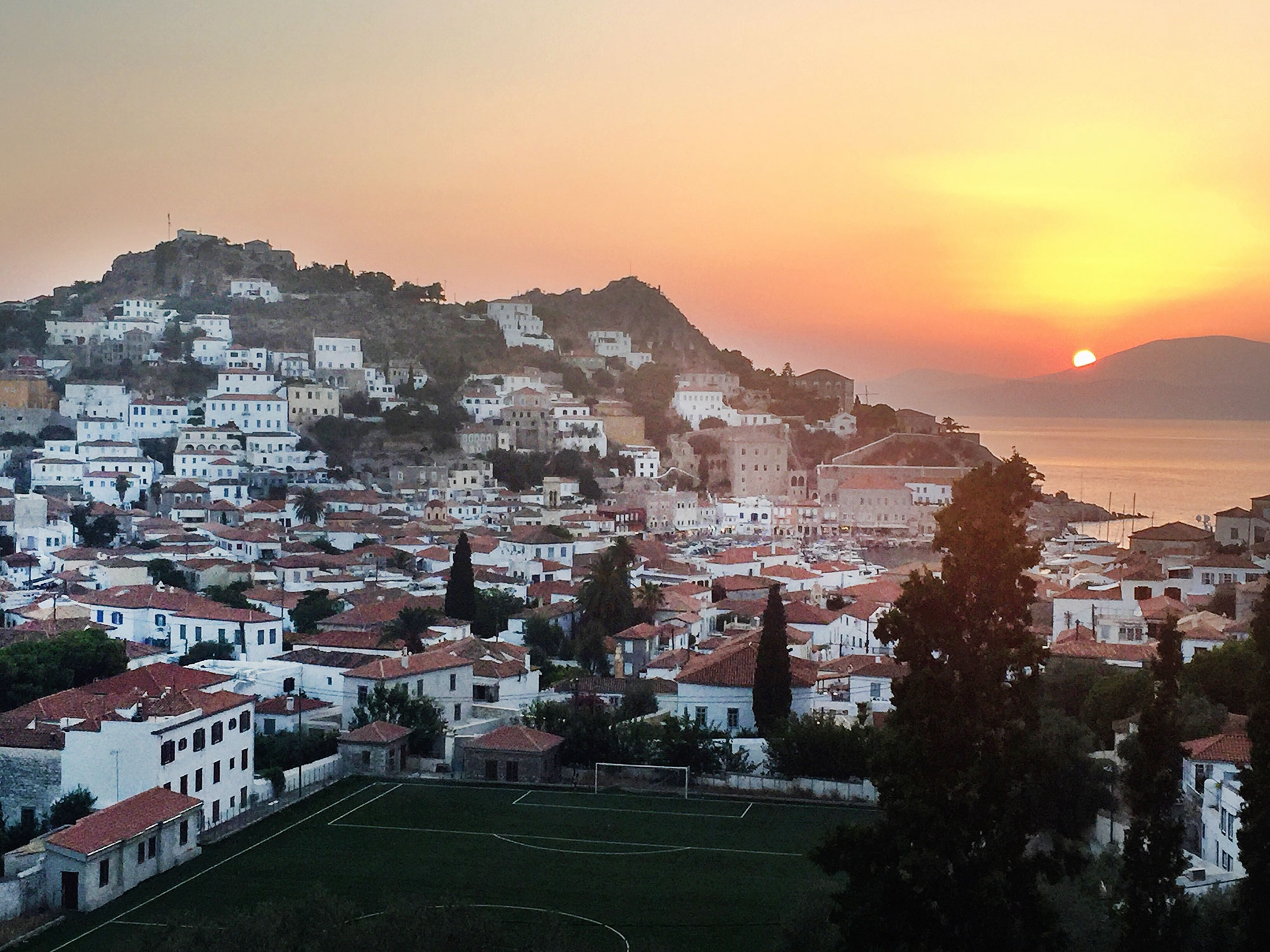 A view of the sunset over a sea of white buildings with terracotta roofs