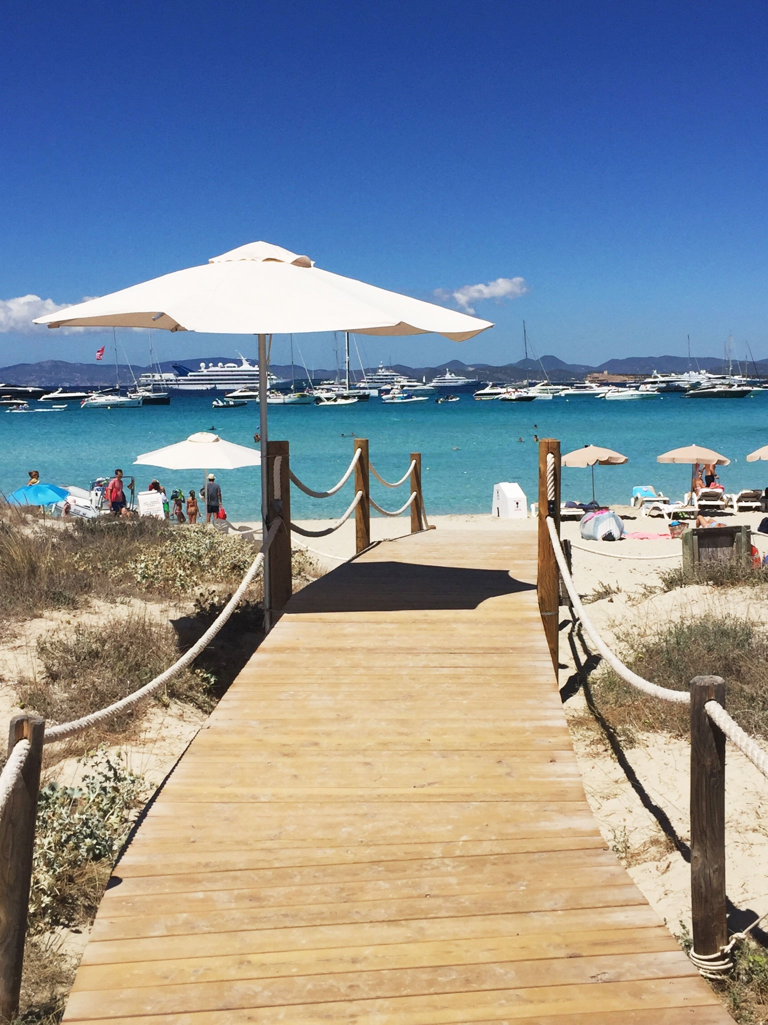 Beachside restaurant, Juan Y Andreas in Formentera, leads down to a bright blue ocean dotted with super yachts