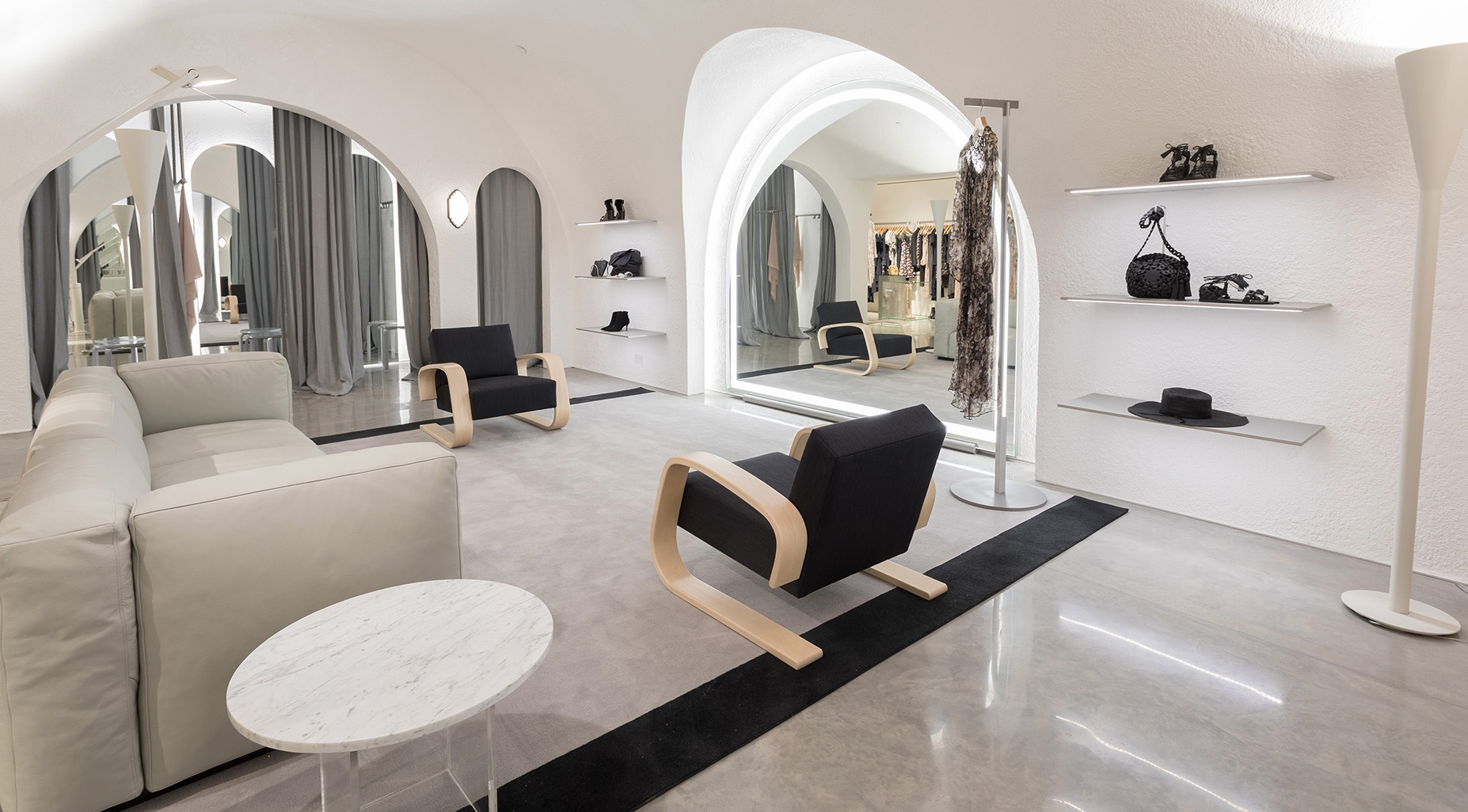 An informal lounge room to the fitting rooms featuring an Italian leather couch and modern chairs