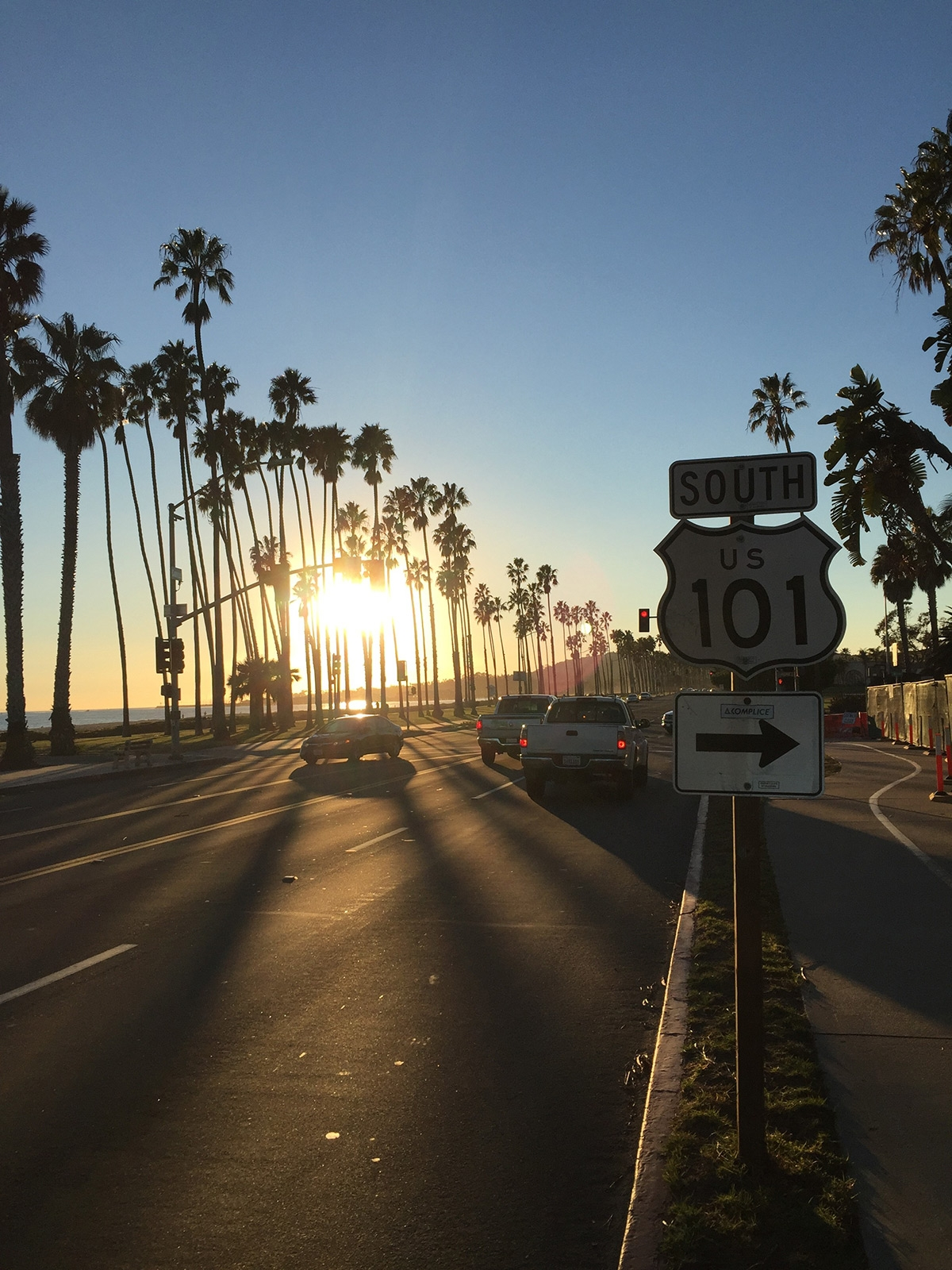 The seaside road at Santa Barbara contains traffic, tall palms and a sign for Route 101