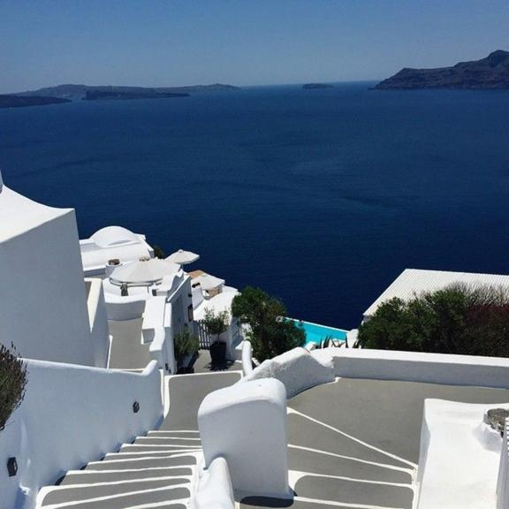 High up on the mountain in Santorini amongst the white buildings and calm blue ocean