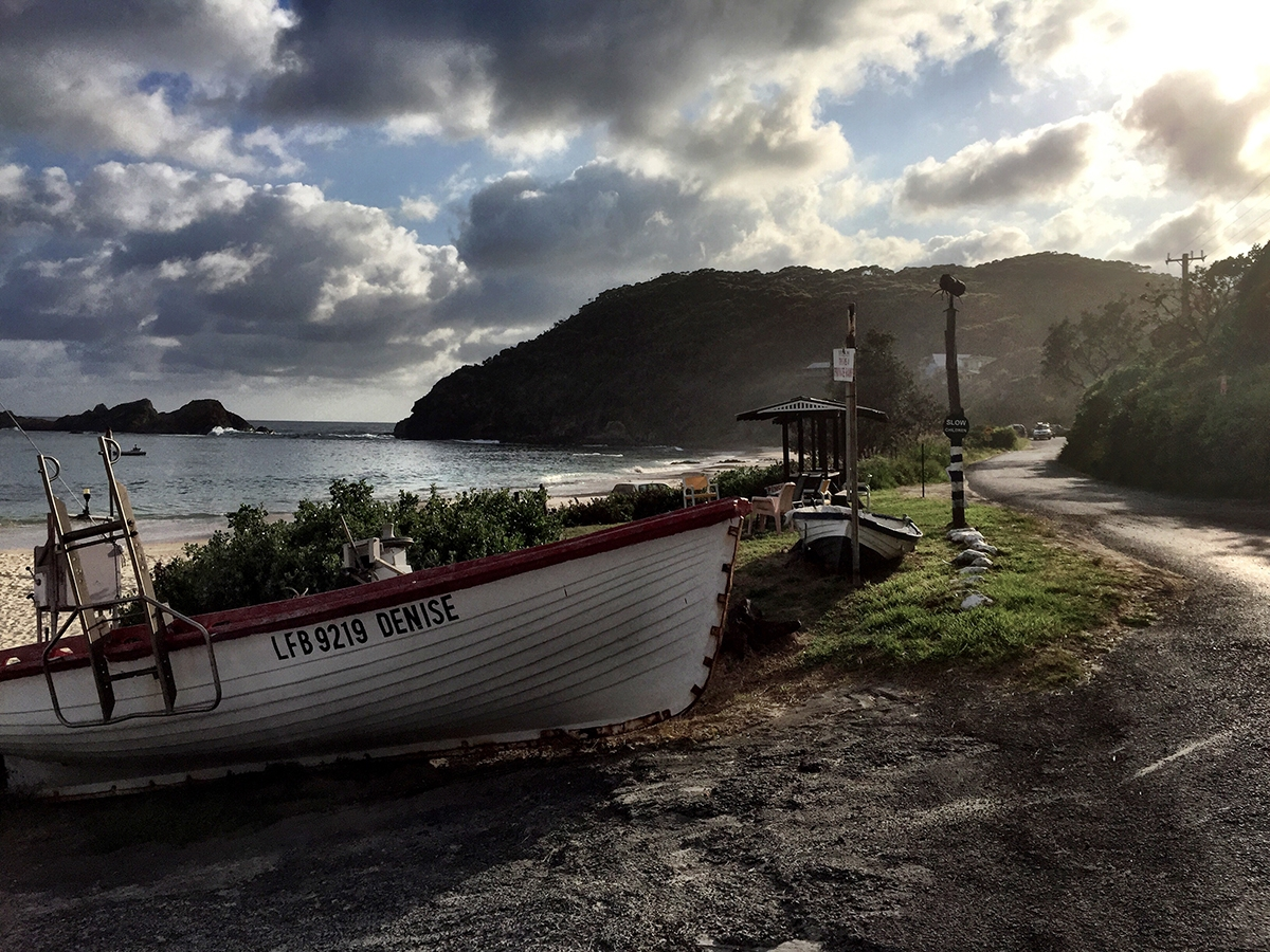 Clouds roll over a boat docked on the shoreline