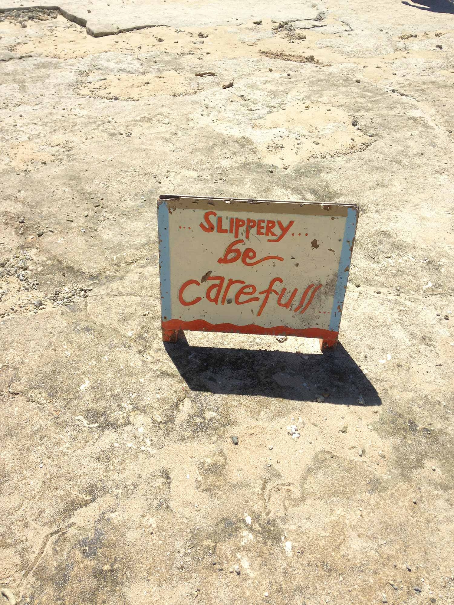 A hand painted sign on a rock that reads 'Slippery… Be Careful!""