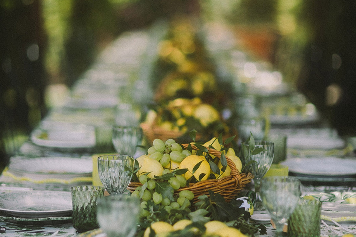 A long rectangular table has been set for lunch with wicker baskets of lemons and grapes as the centerpiece, light green crystal glasses and patterned plate settings.