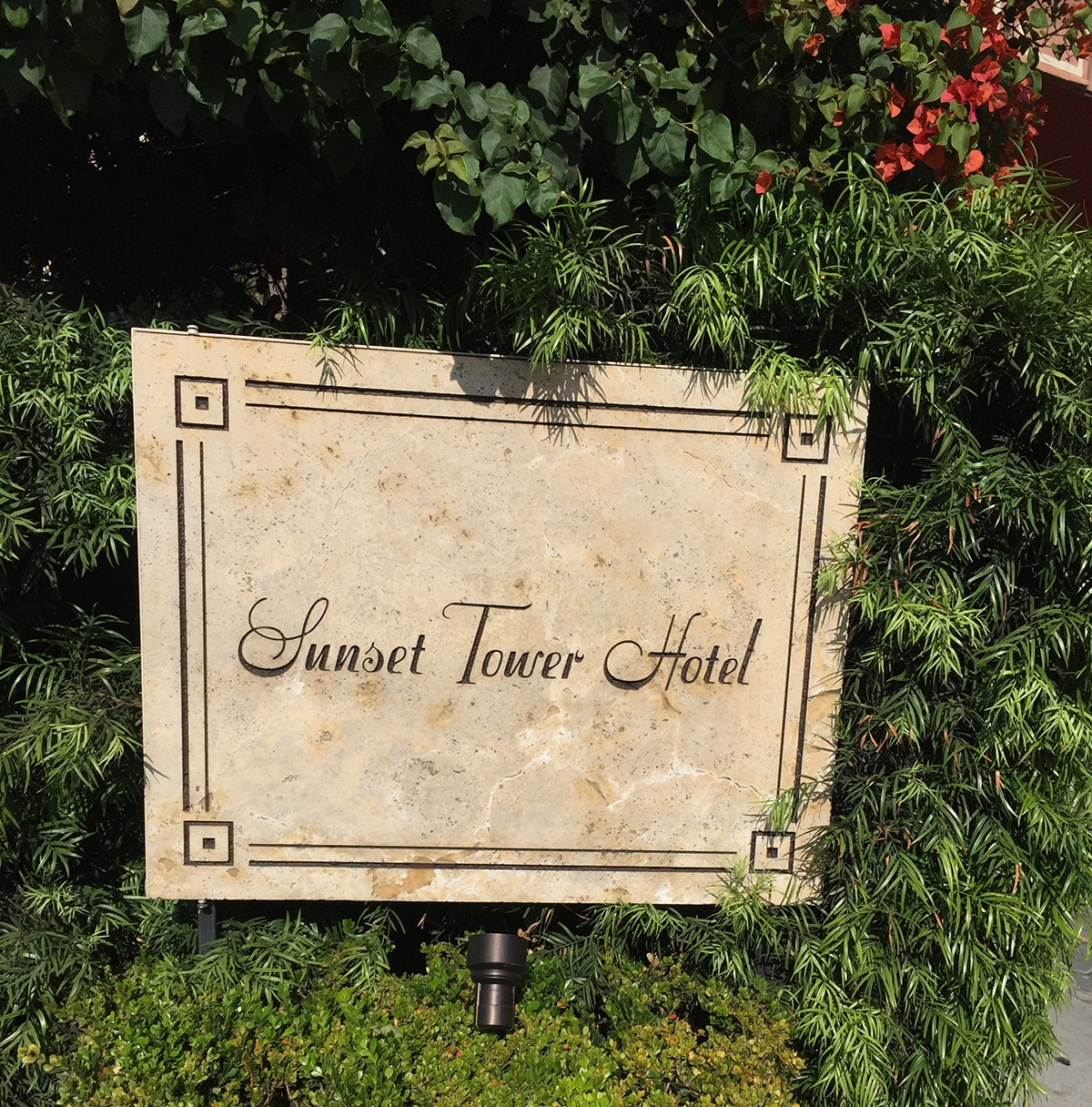An outdoor sign perched in a garden that reads, 'Sunset Tower Hotel'