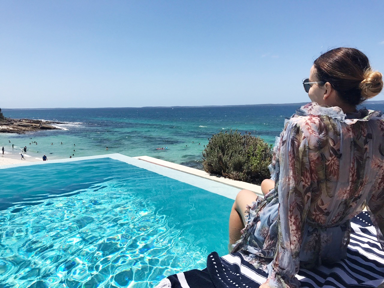 Marnie sitting by the pool, looking down at the turquoise sea below