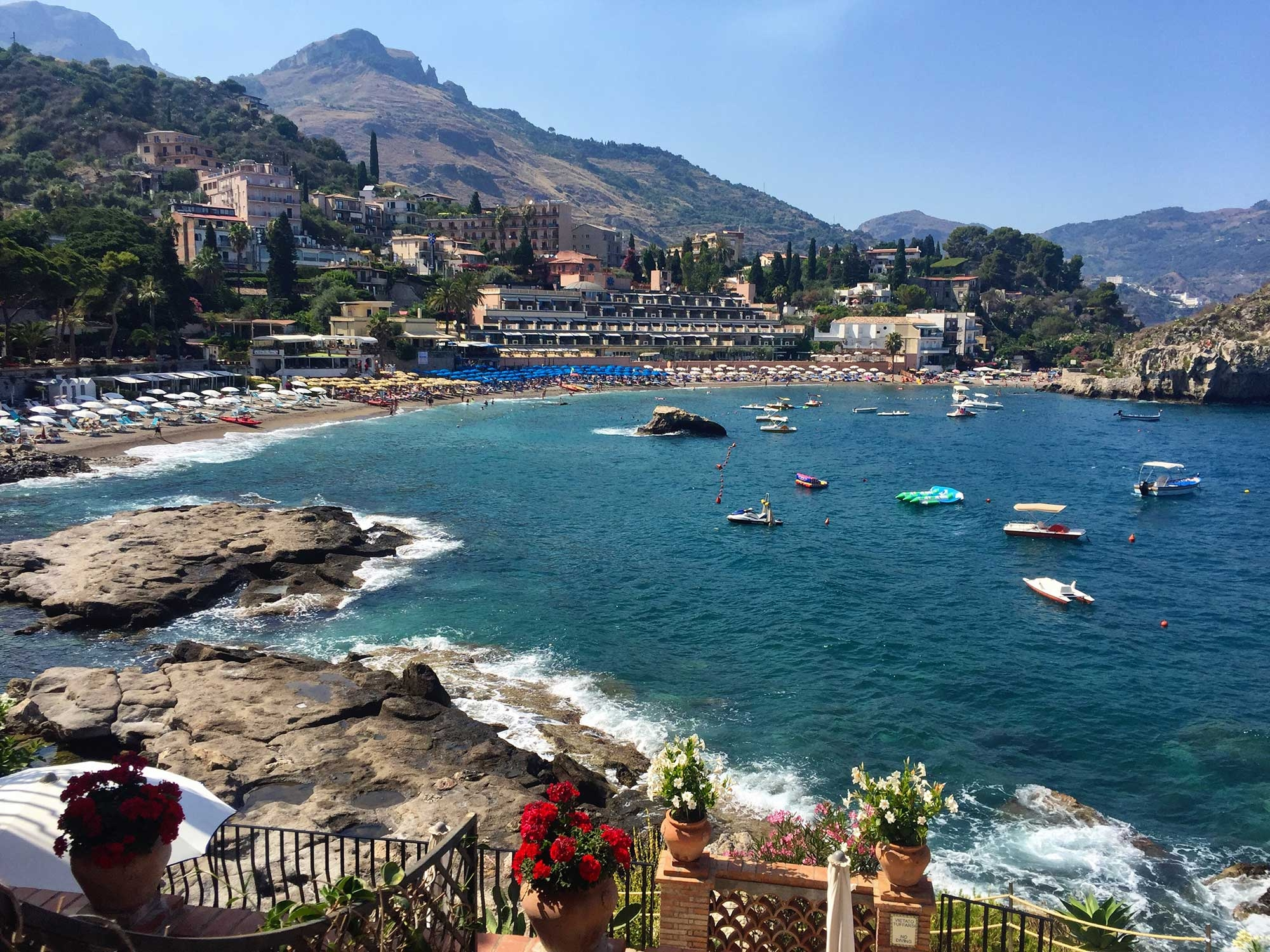 Large mountains surround the Taormina coast which is lined with sun loungers and beach umbrellas