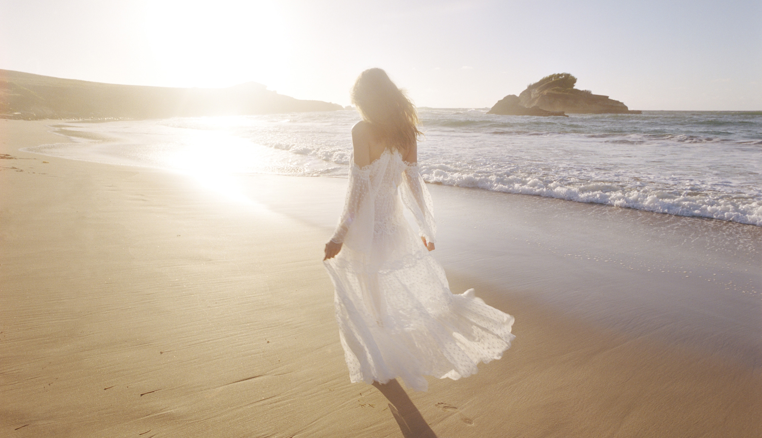 Walking along the beach in Look 1 of the Capsule Collection