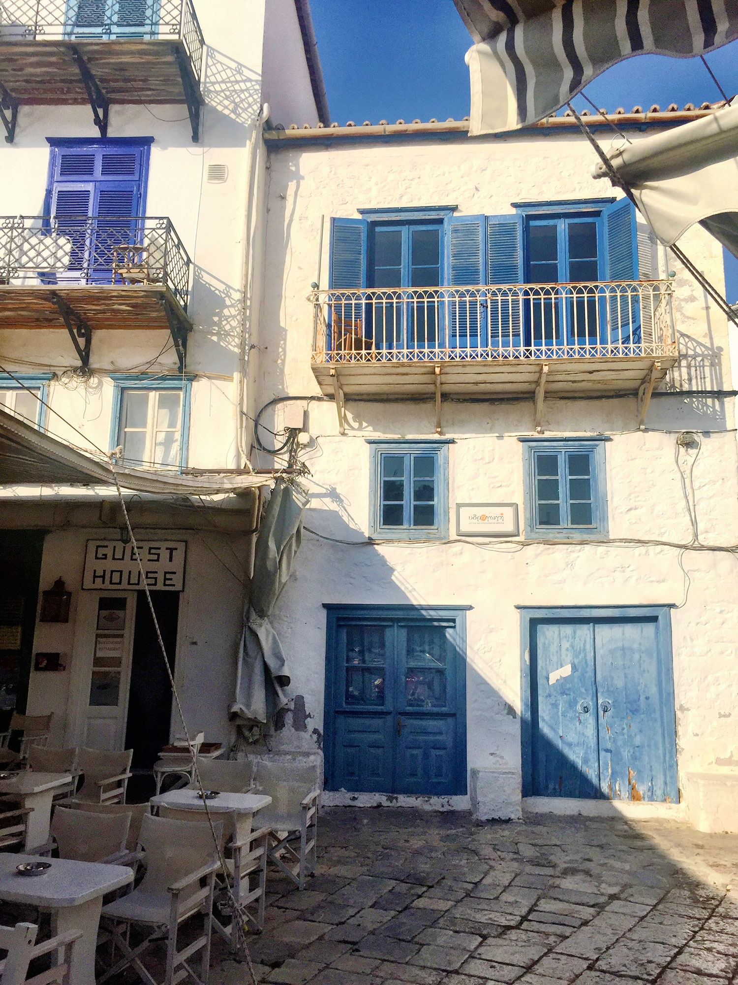A white Greek building with faded blue doors, windows and shutters