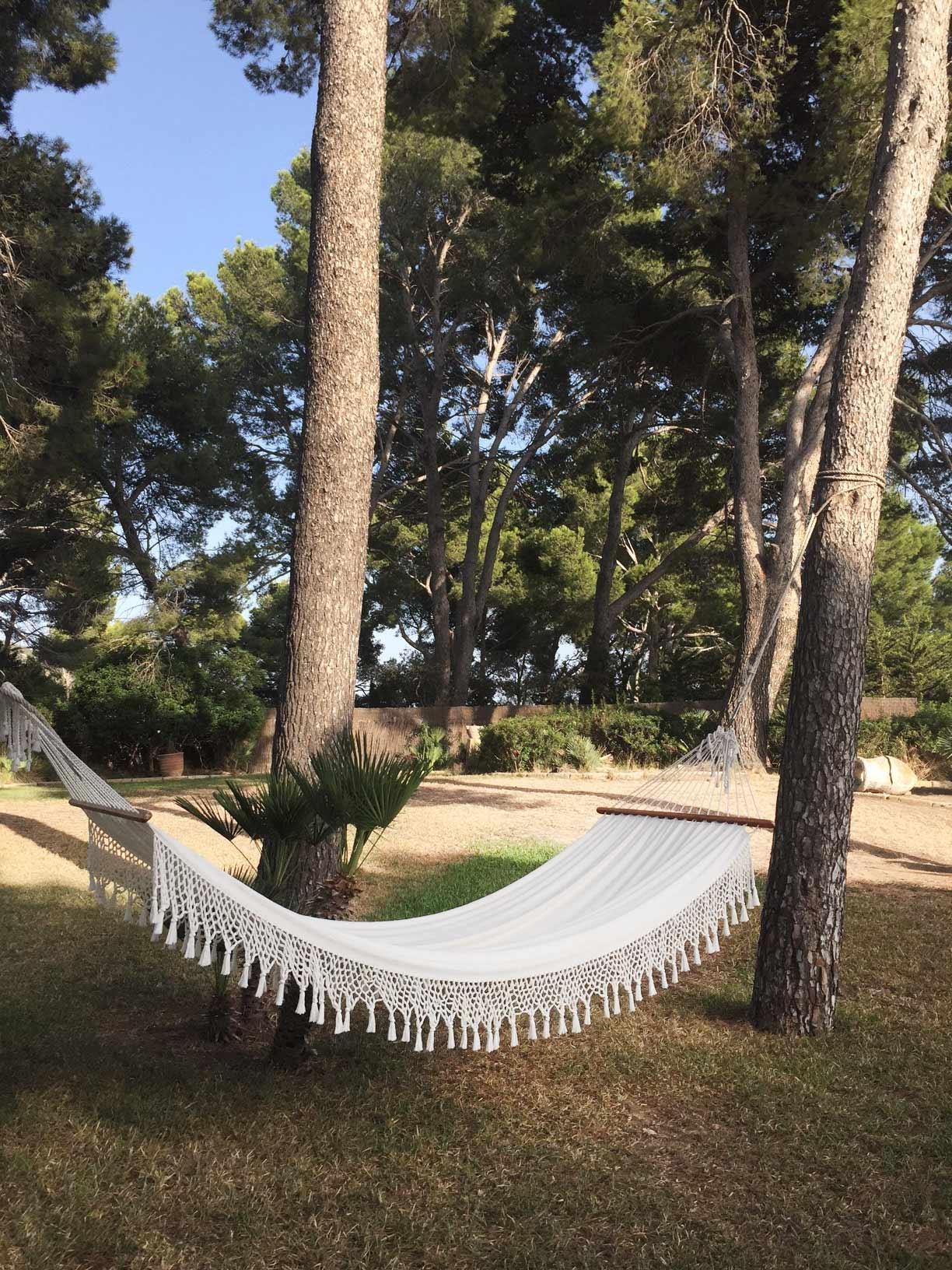 A white hammock hangs between trees in a garden