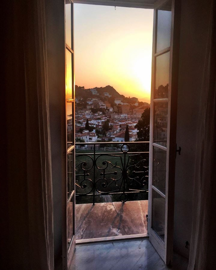 Open French doors lead out to a small balcony that overlooks a sun setting on terracotta roof houses